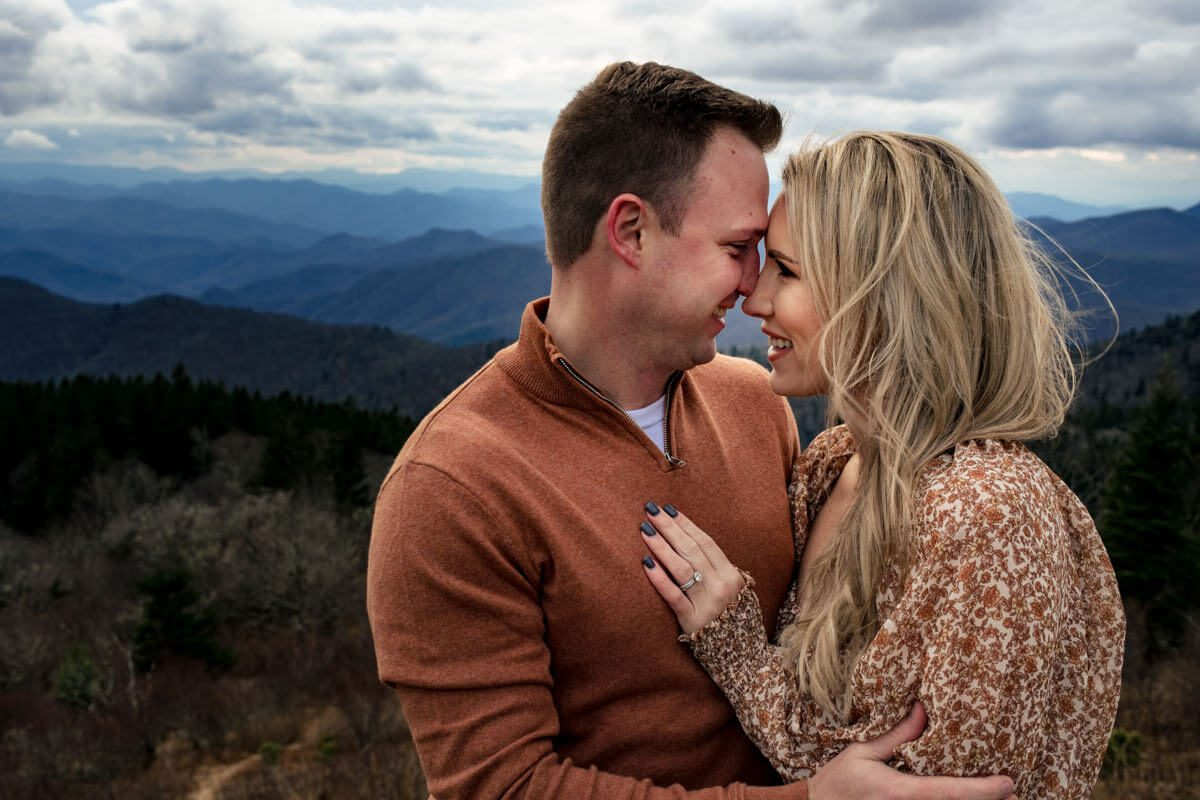 Couple embracing for their engagement photoshoot with the mountains in the background