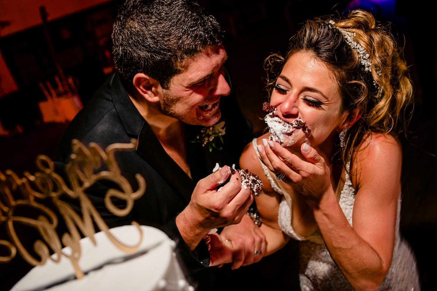 bride and groom having fun with wedding cake in miami