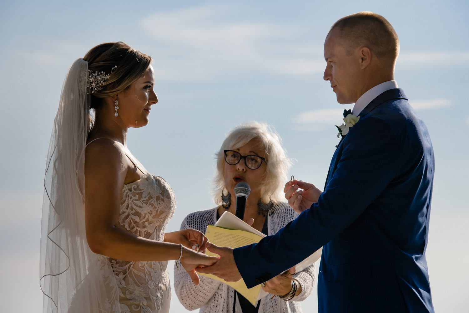 groom giving ring to bride during ceremony