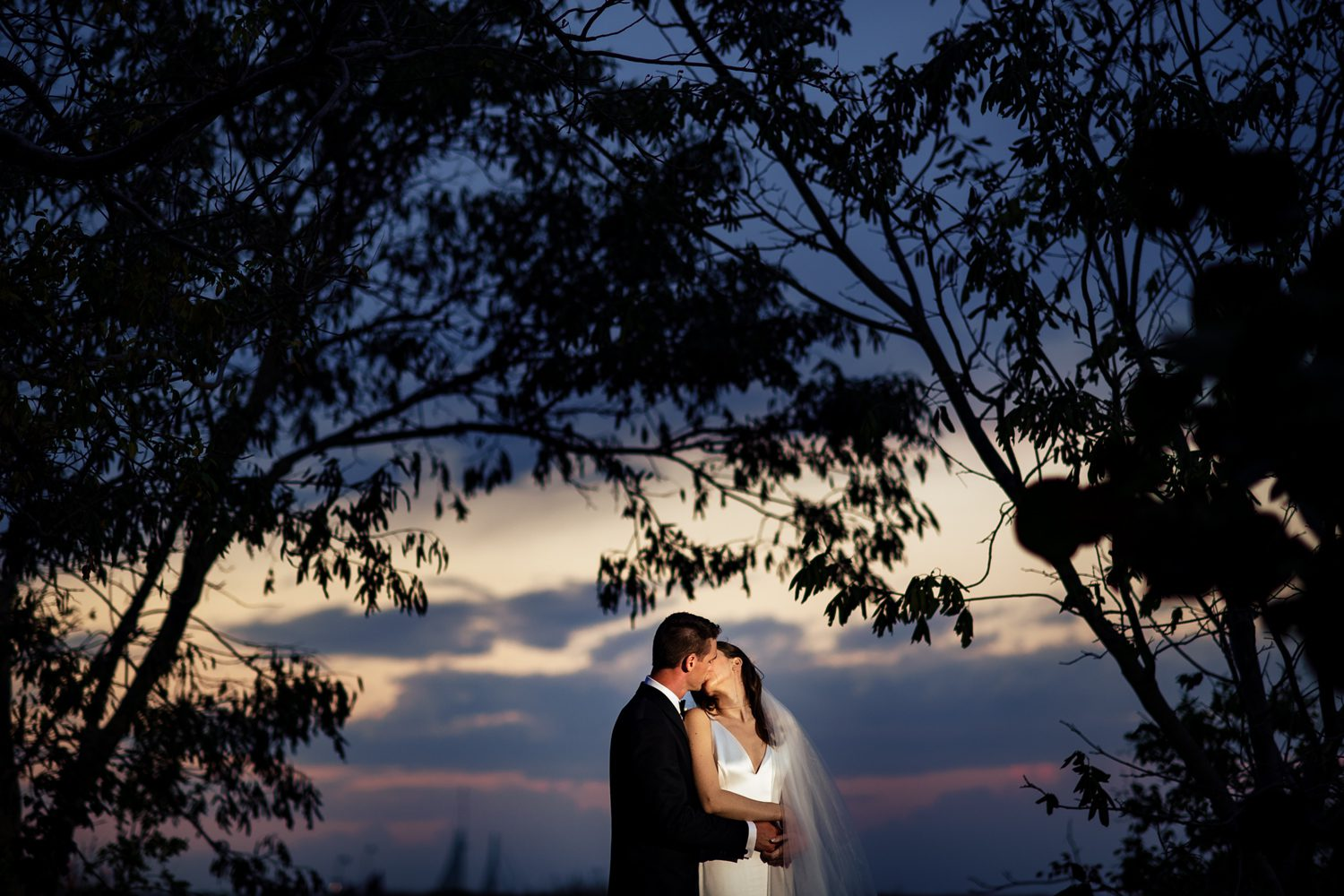 sunset kiss between bride and groom