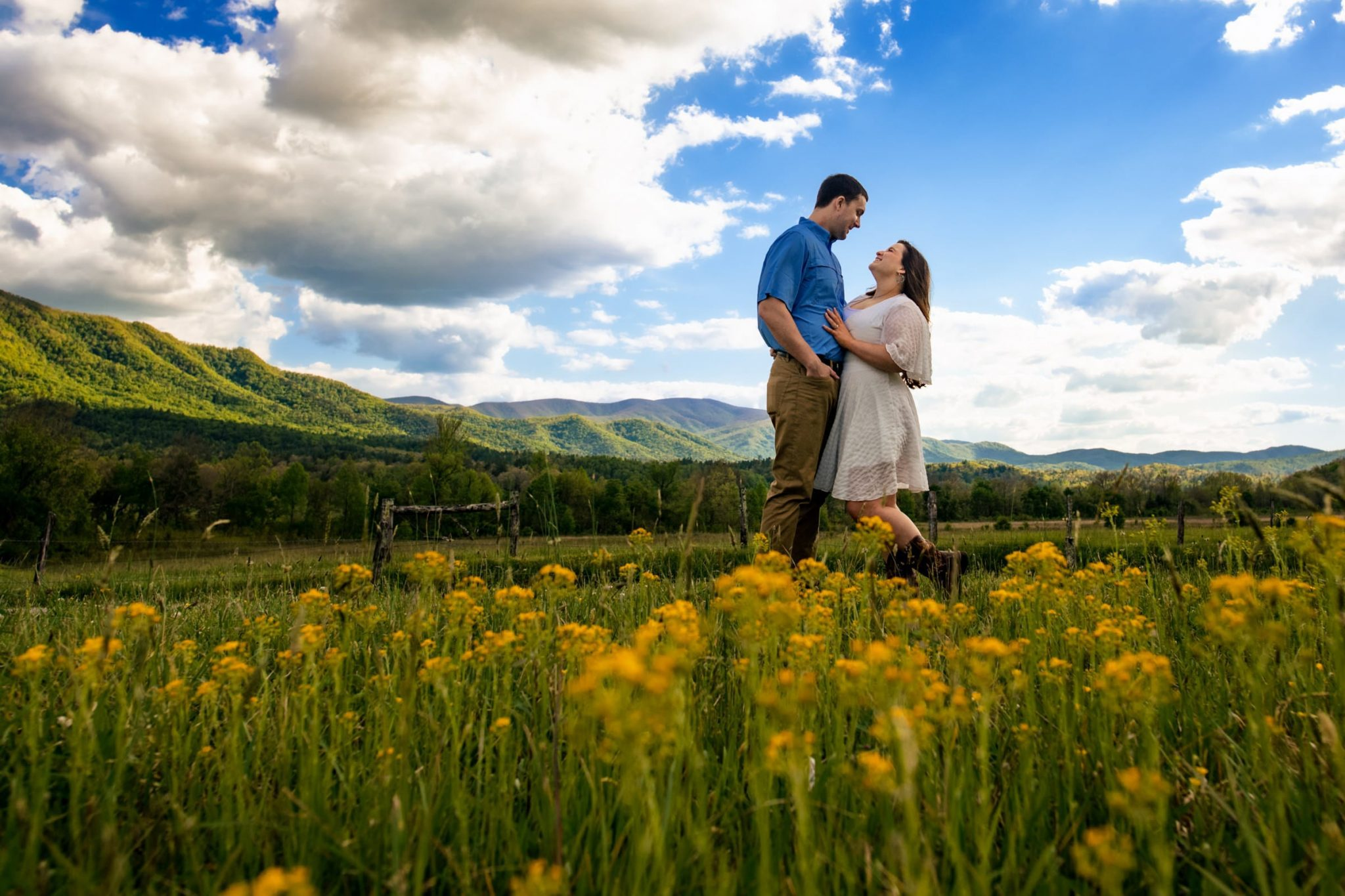 Couple holding hands during an engagement photoshoot in among flowers