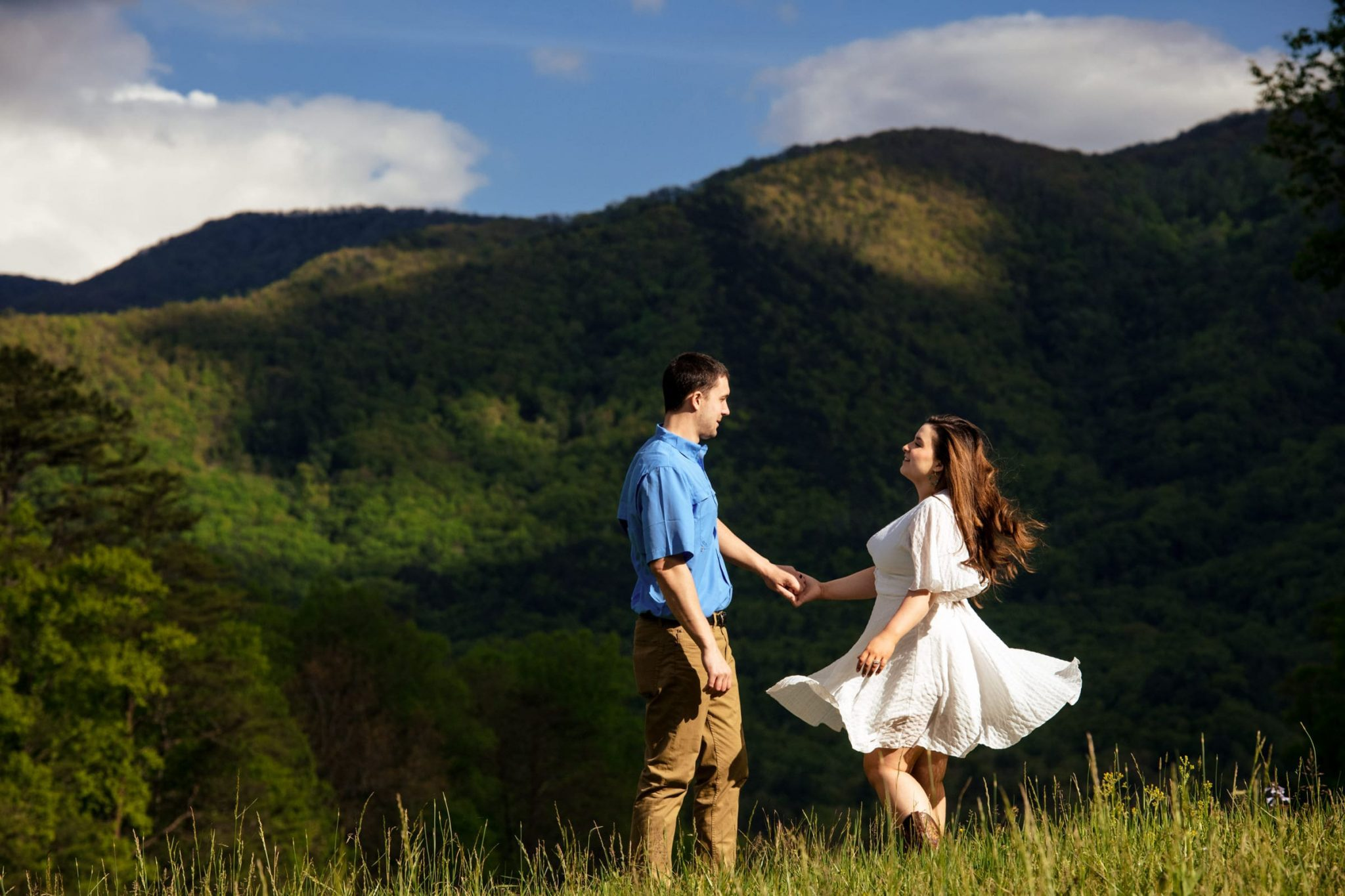 Couple's engagement photo session, walking through a meadow in the mountains