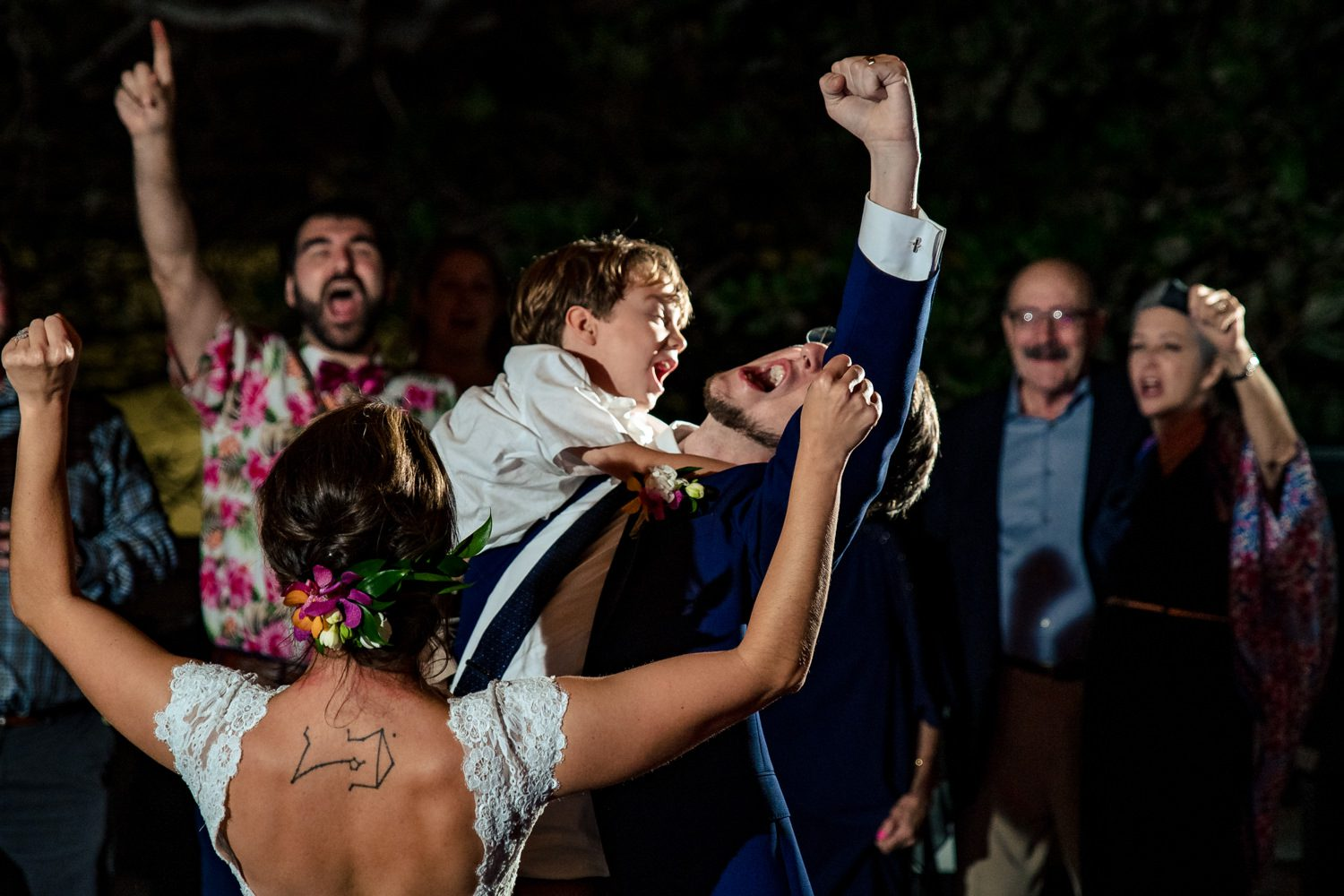 Groom holding a young child while dancing