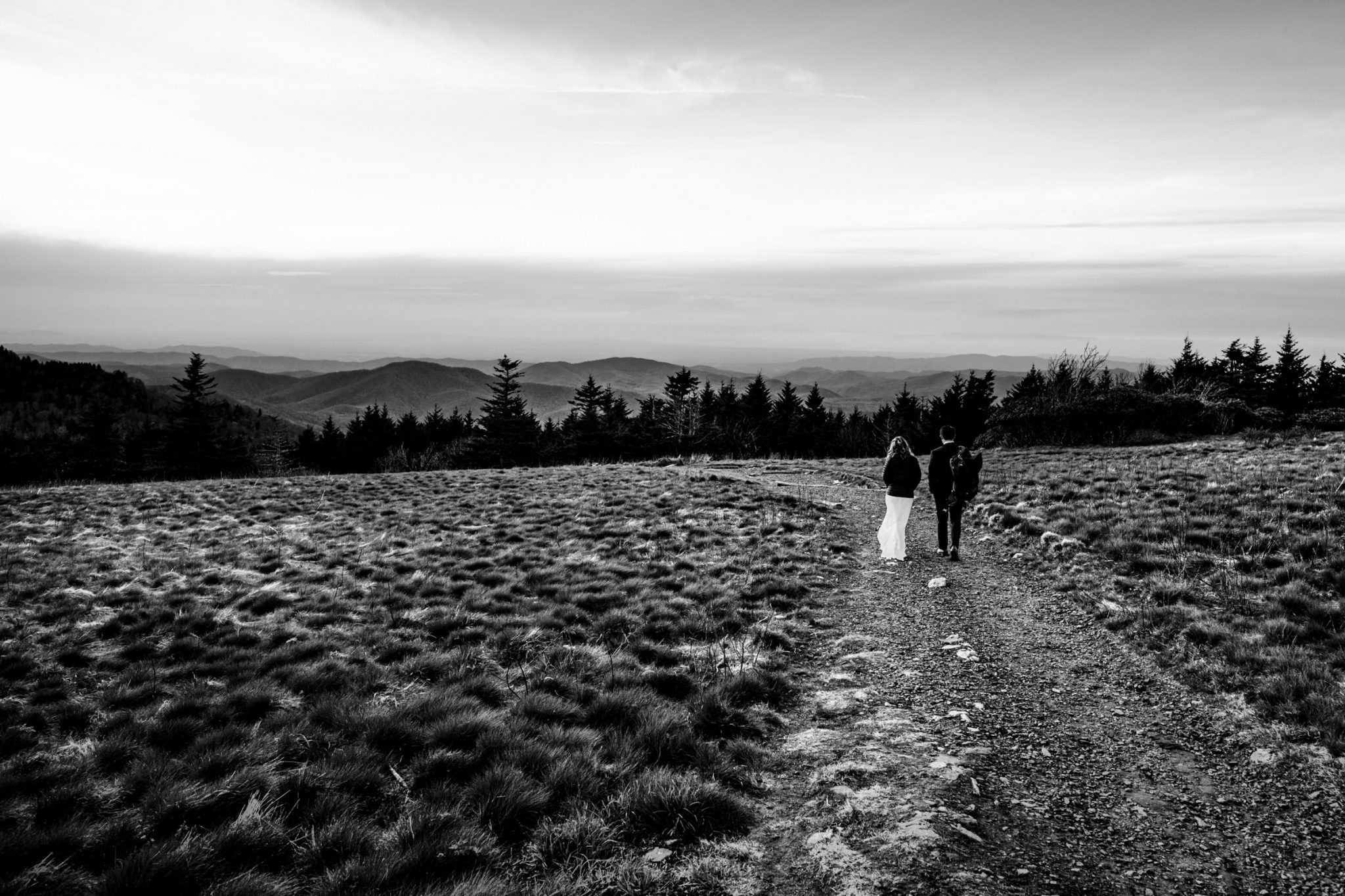 Black and white photo of couple walking along a path