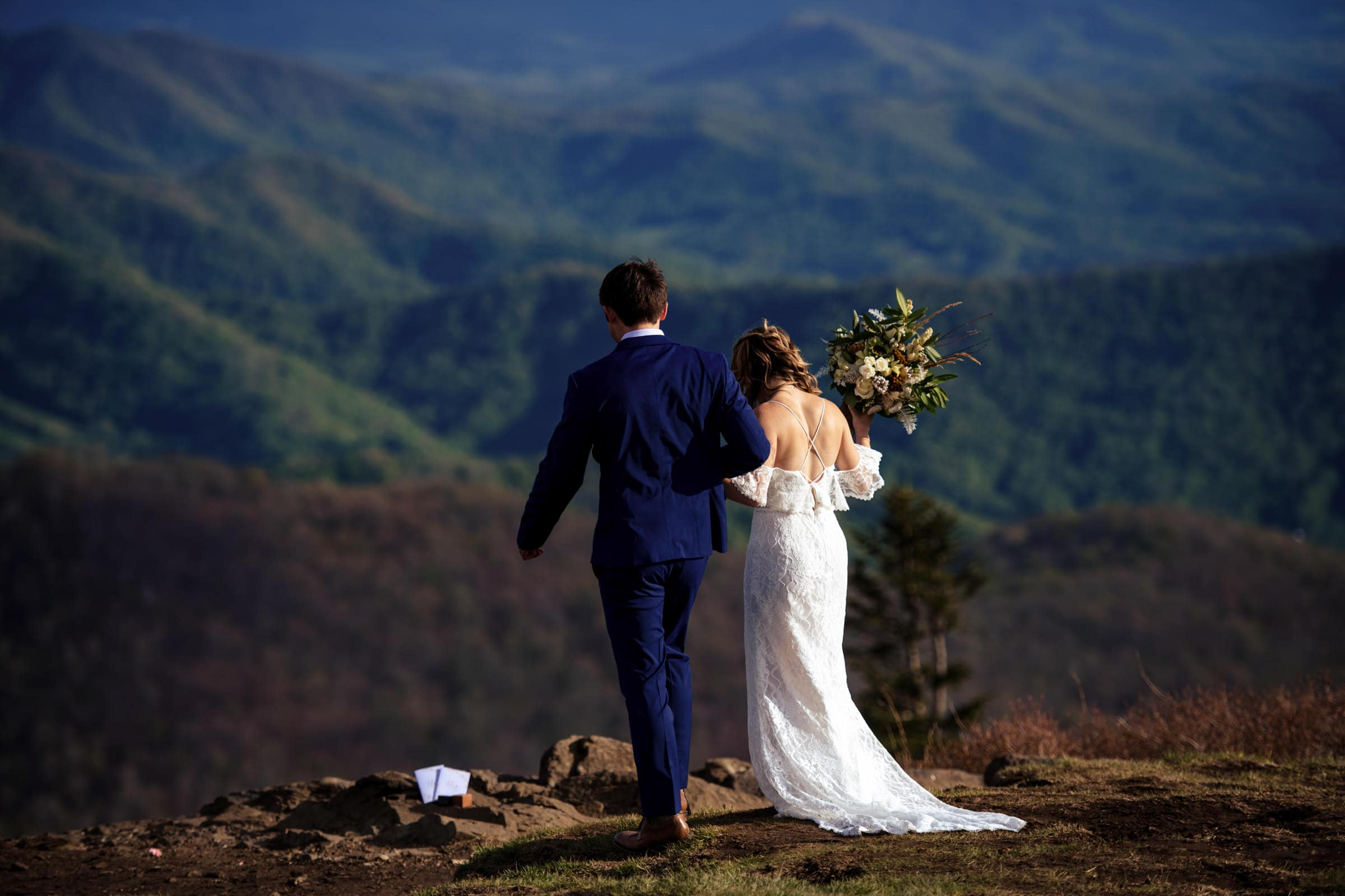 A couple facing away from the camera during their elopement ceremony in the roan mountains at carvers gap