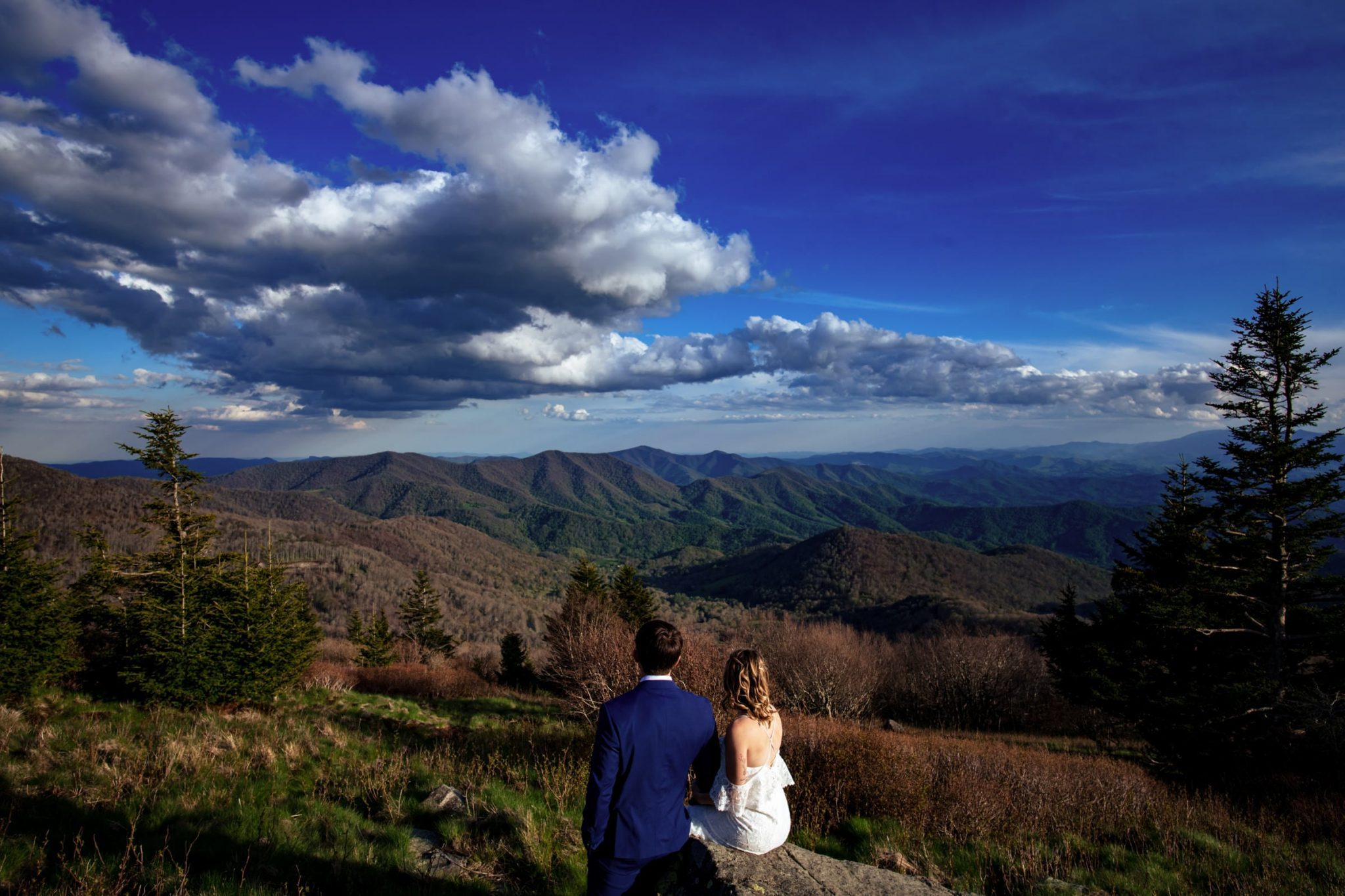 Couple sitting on a mountain peak during elopement ceremony in Asheville