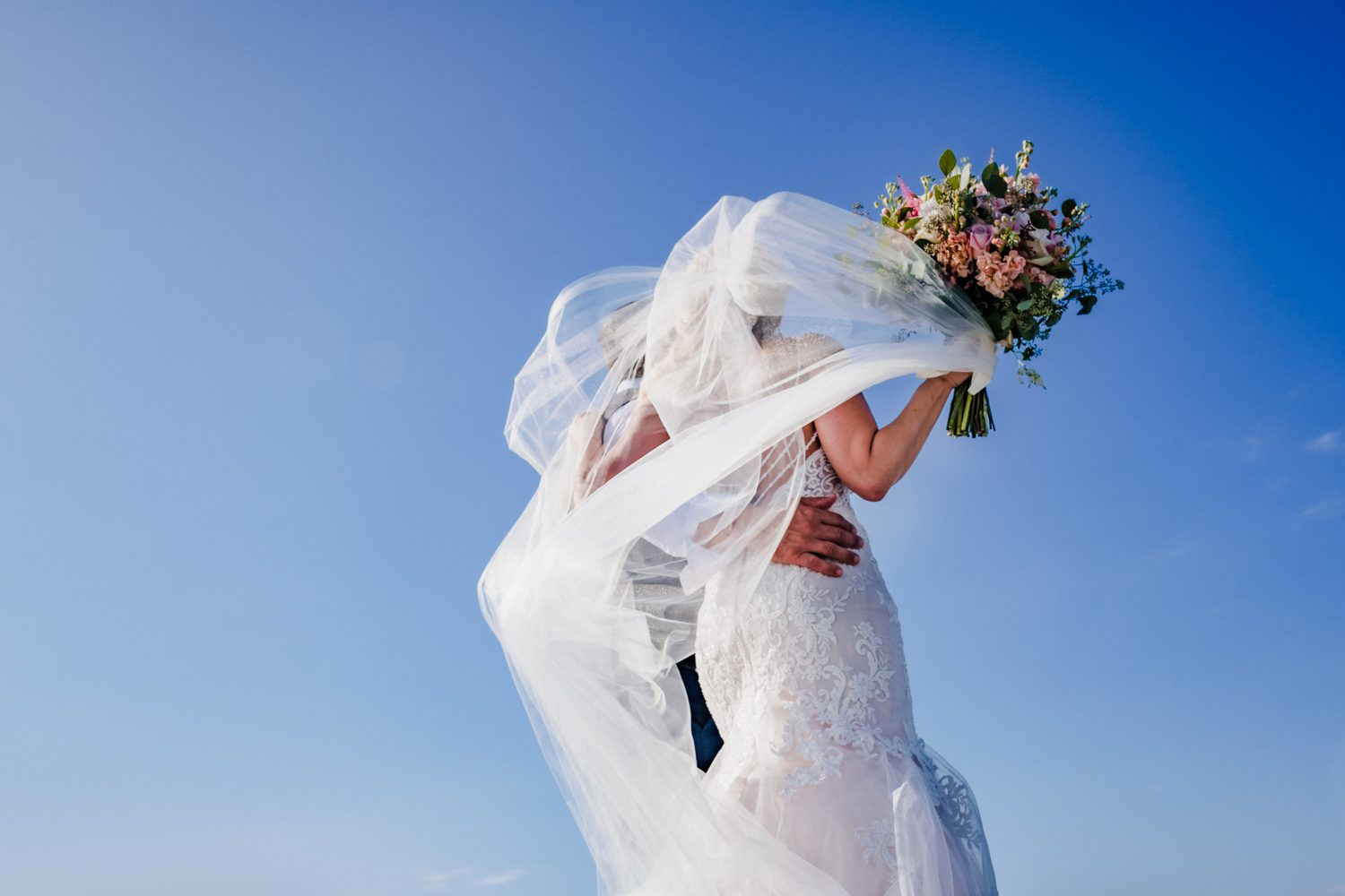 bride with her veil blowing in the wind at fort zachary taylor