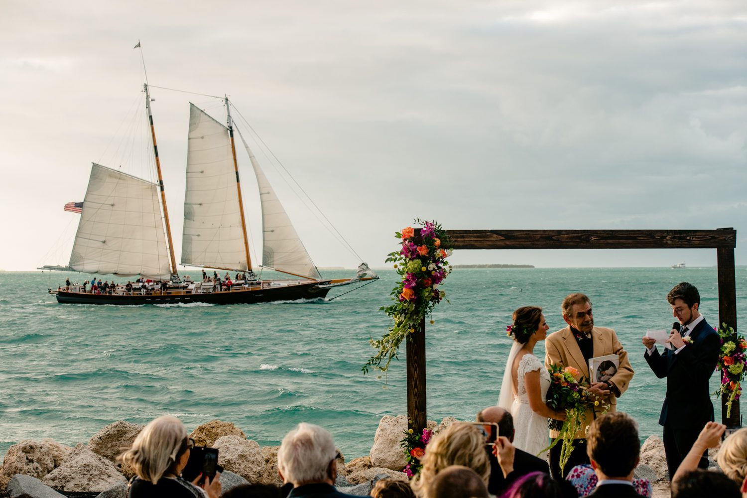 Boat in the background of a beach wedding at fort zachary taylor