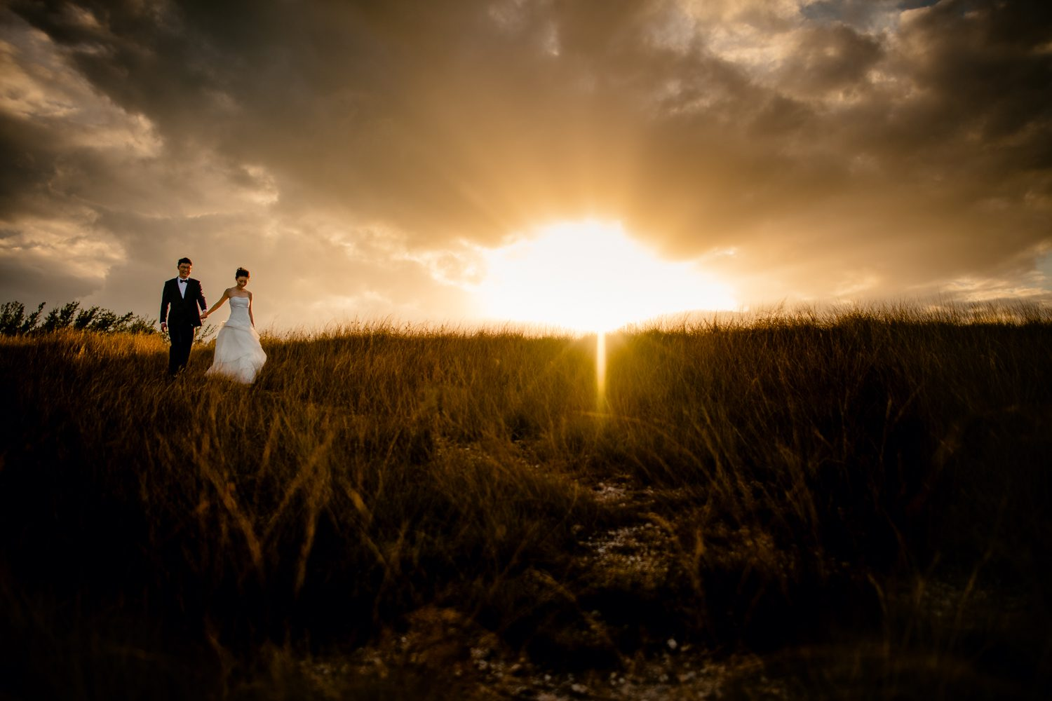 Bride and groom holding hands in a field at sunset at fort zachary taylor