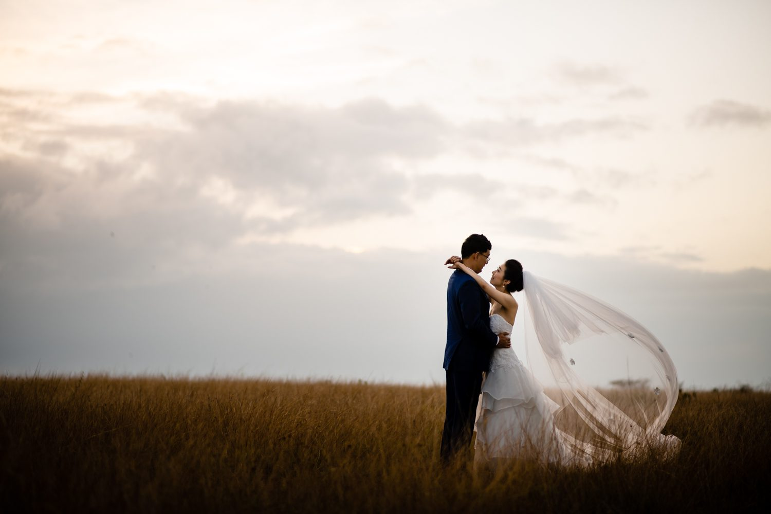 Bride and groom standing in a field embracing at fort zachary taylor