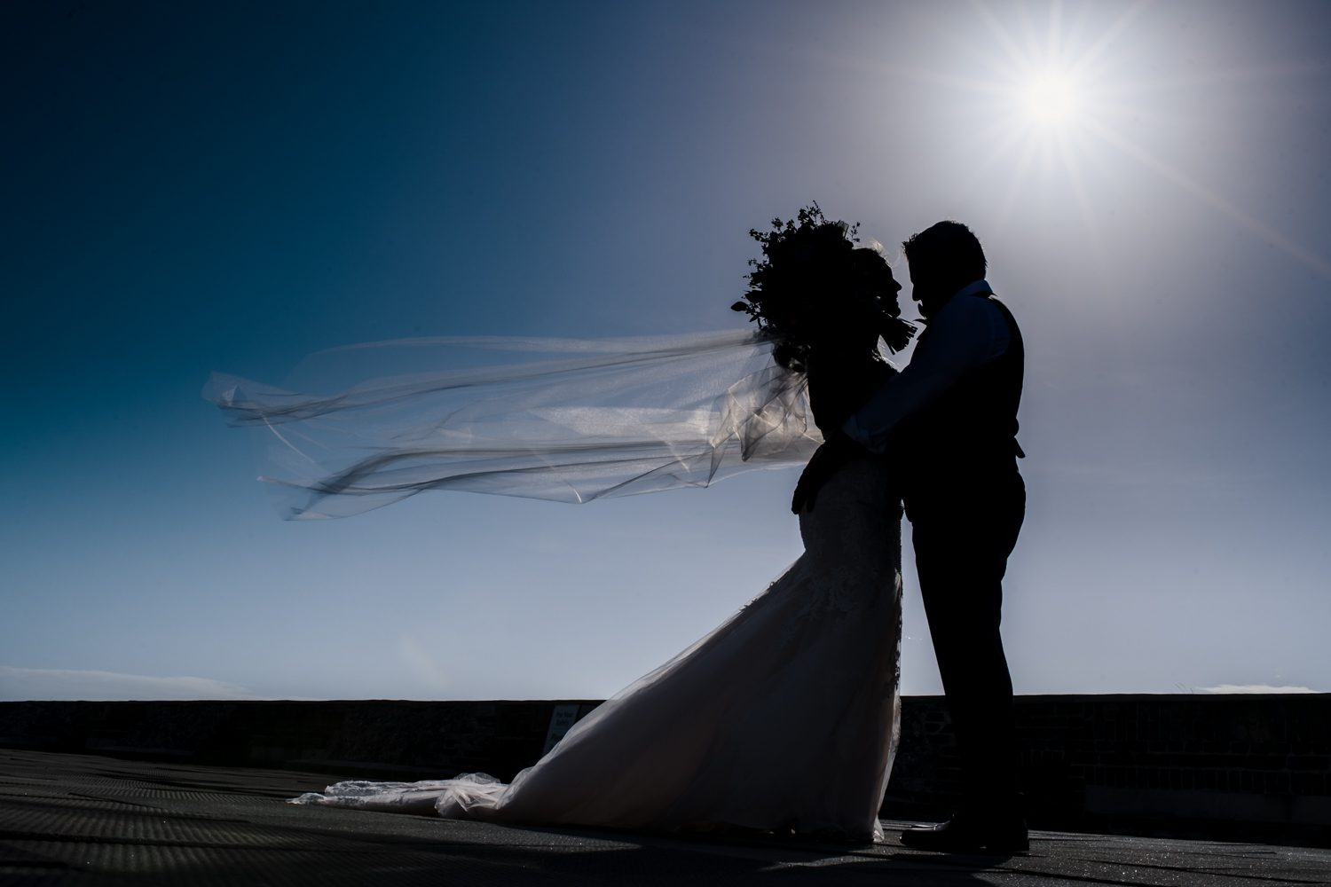 silhouette of bride and groom on windy day at fort zachary taylor