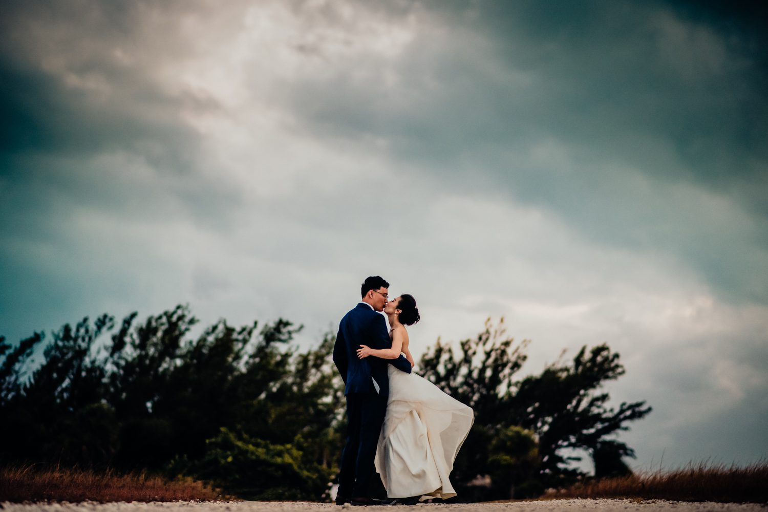 Newlyweds kissing on the beach at fort zachary taylor