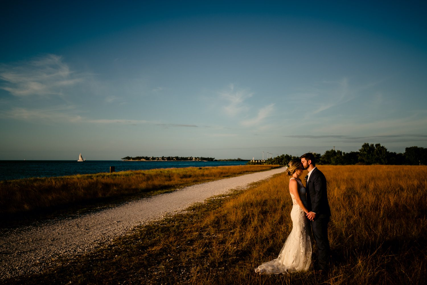 Newlyweds embracing in an open field at fort zachary taylor