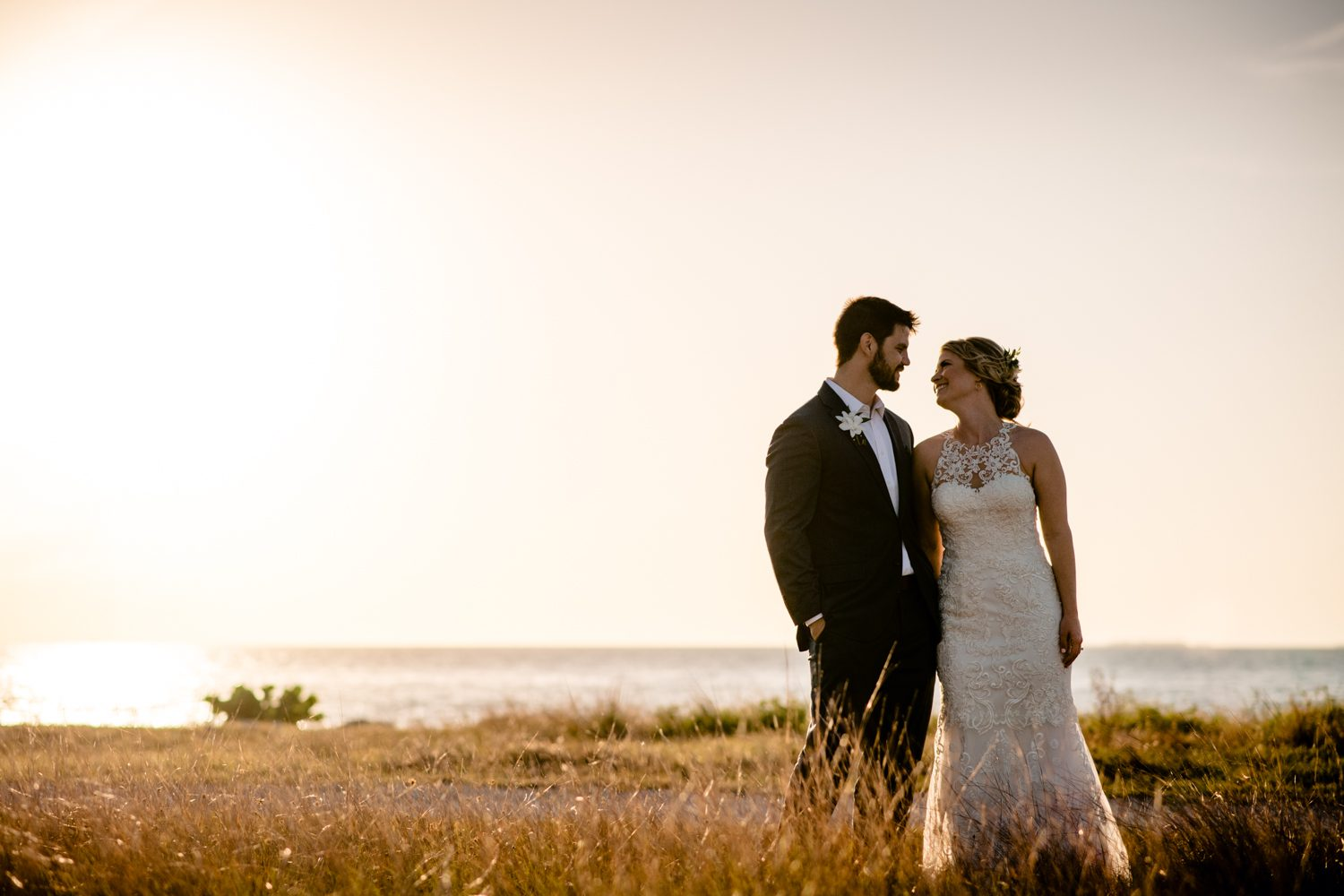 Newlyweds holding hands in a field at fort zachary taylor