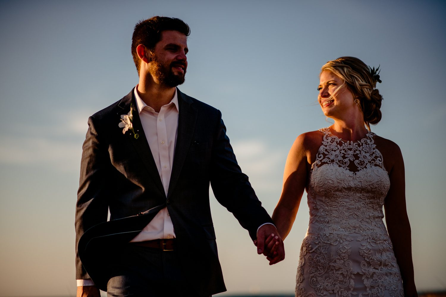 Newlyweds holding hands on the beach at fort zachary taylor