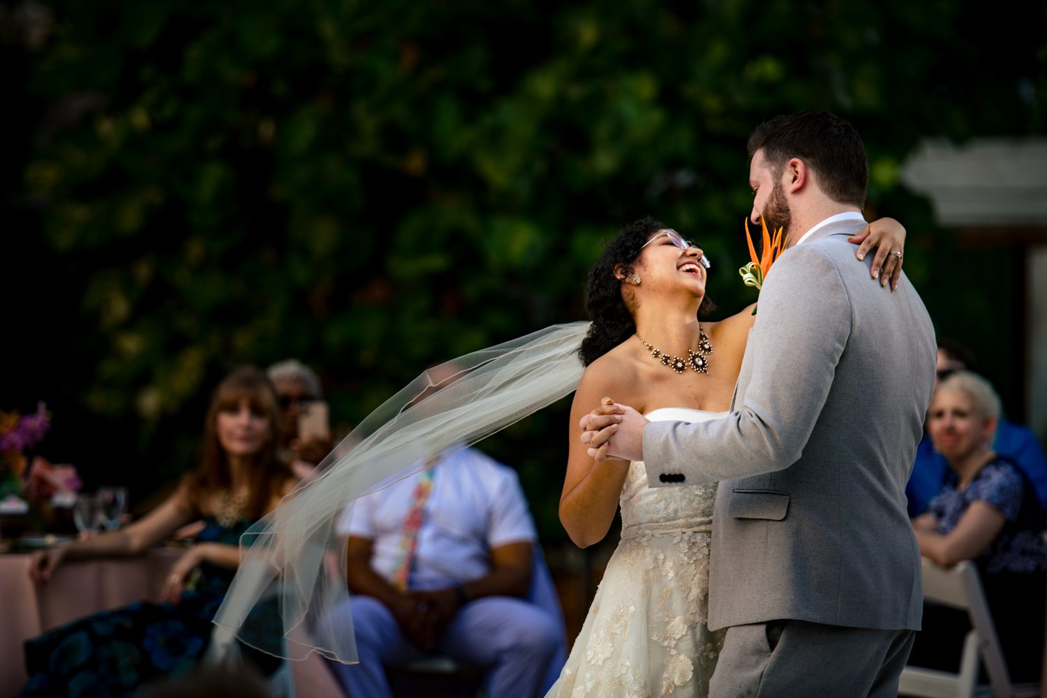 Bride laughing while dancing with her husband