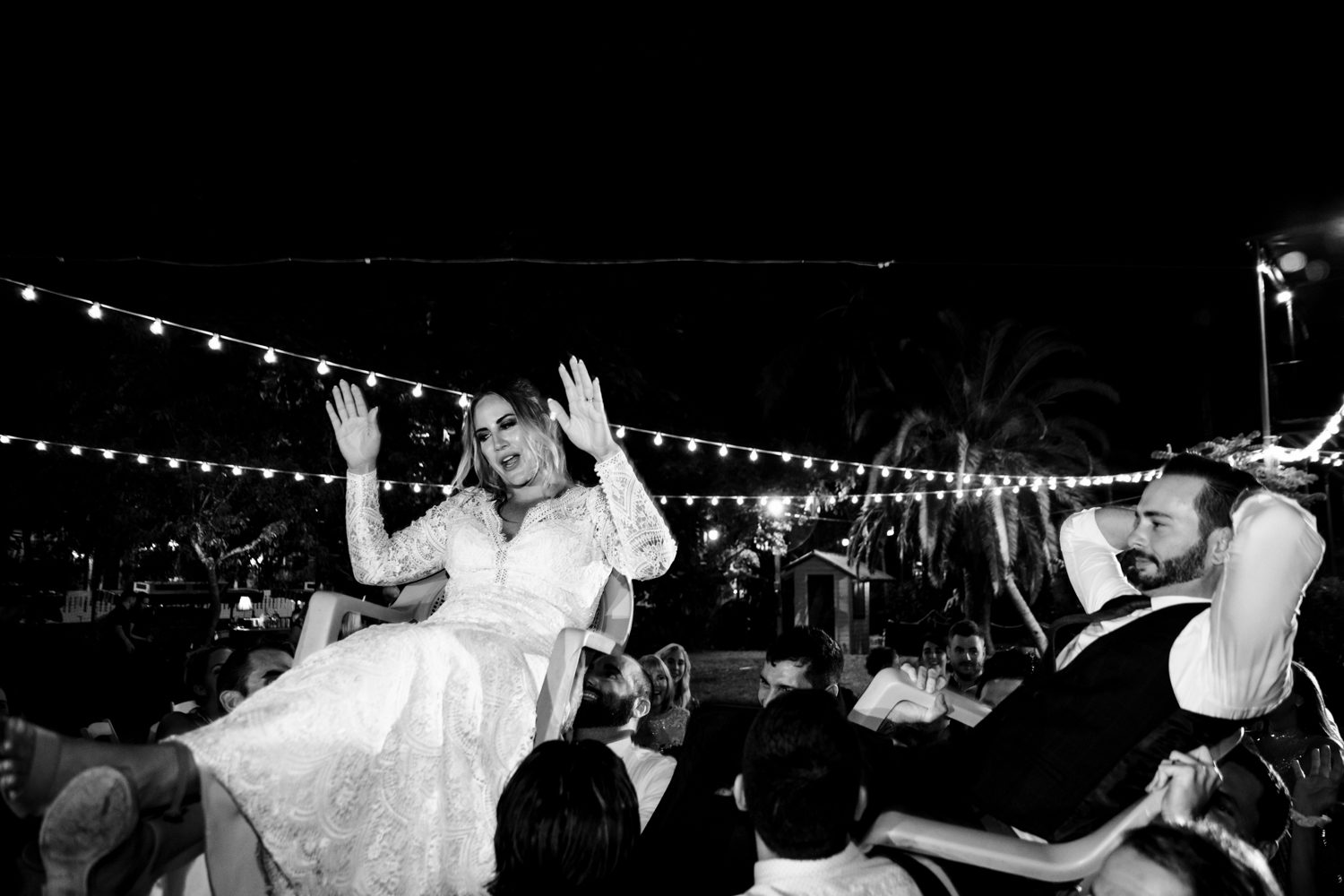 Woman being carried on a chair at her wedding reception