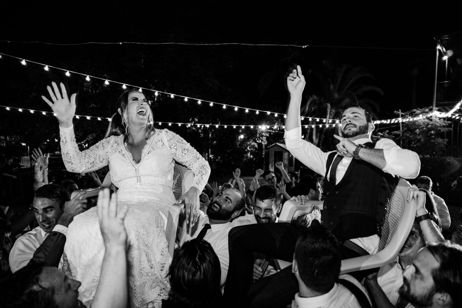 Bride and groom being carried on a chair at her wedding reception