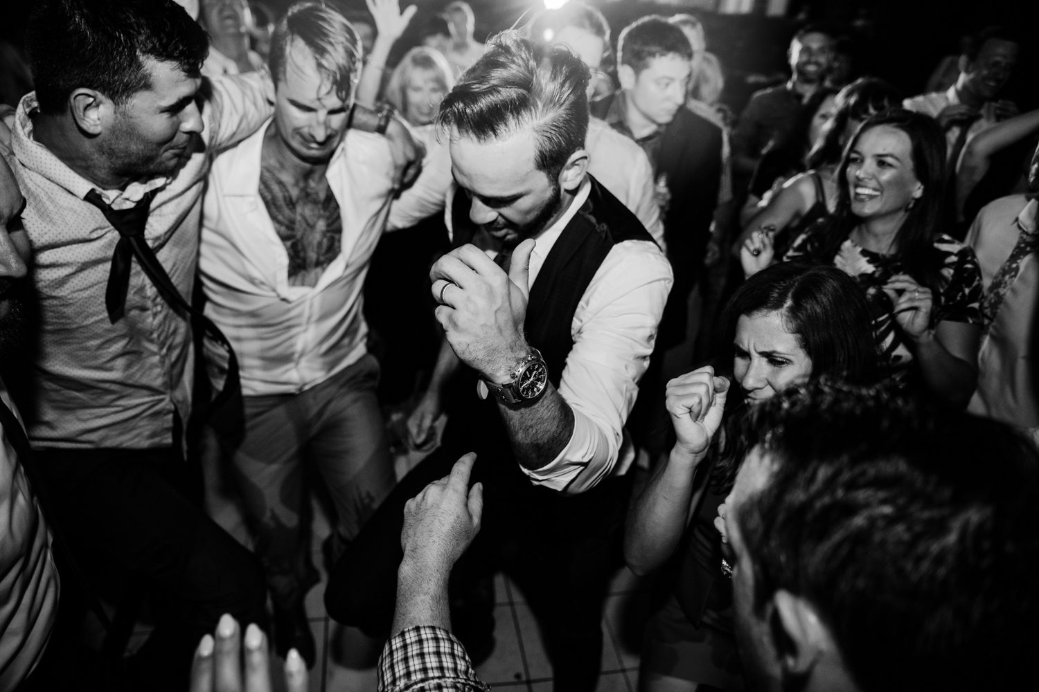 Groom dancing at his wedding reception with friends