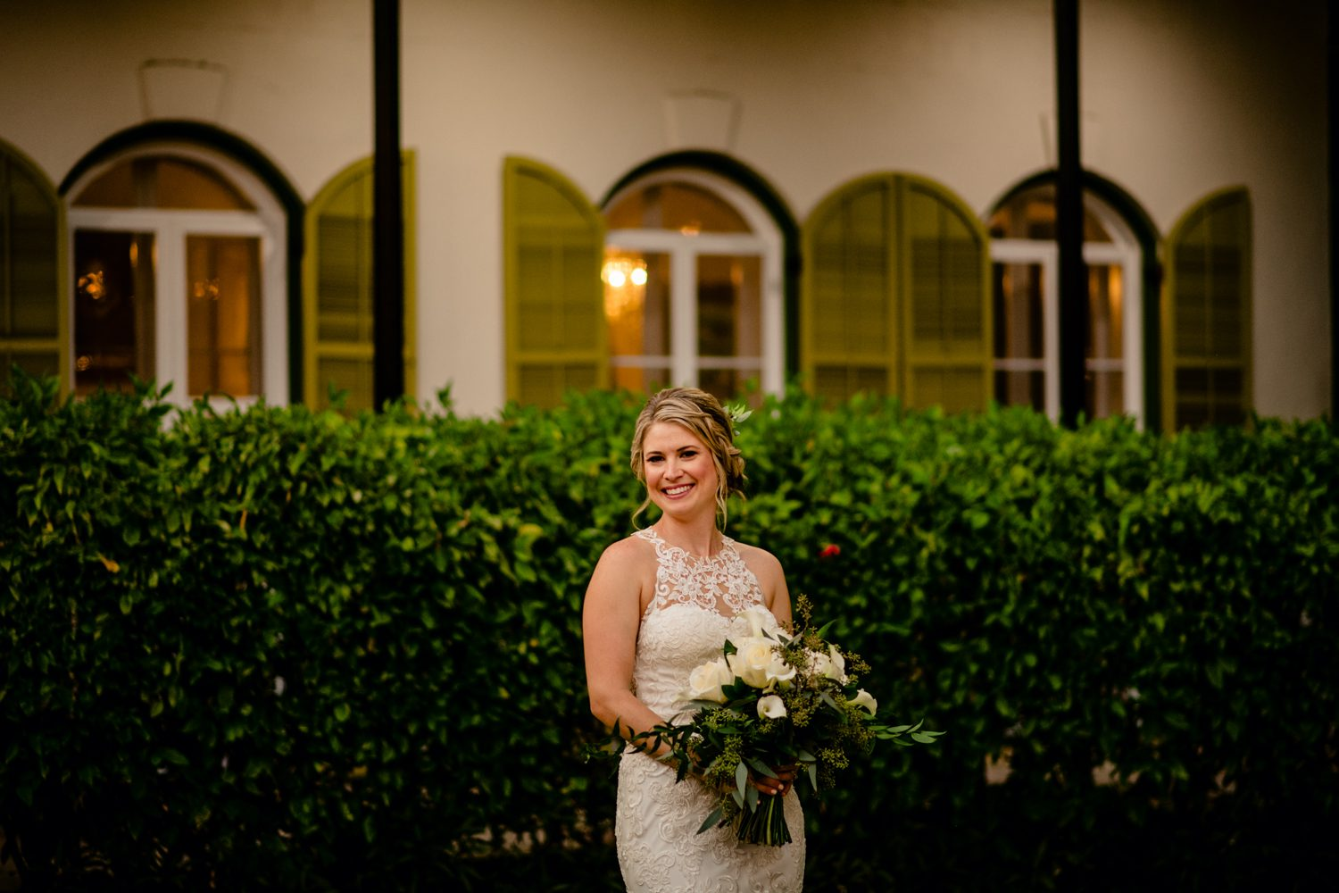 Bride holding her bouquet in front of a bush at hemingway house