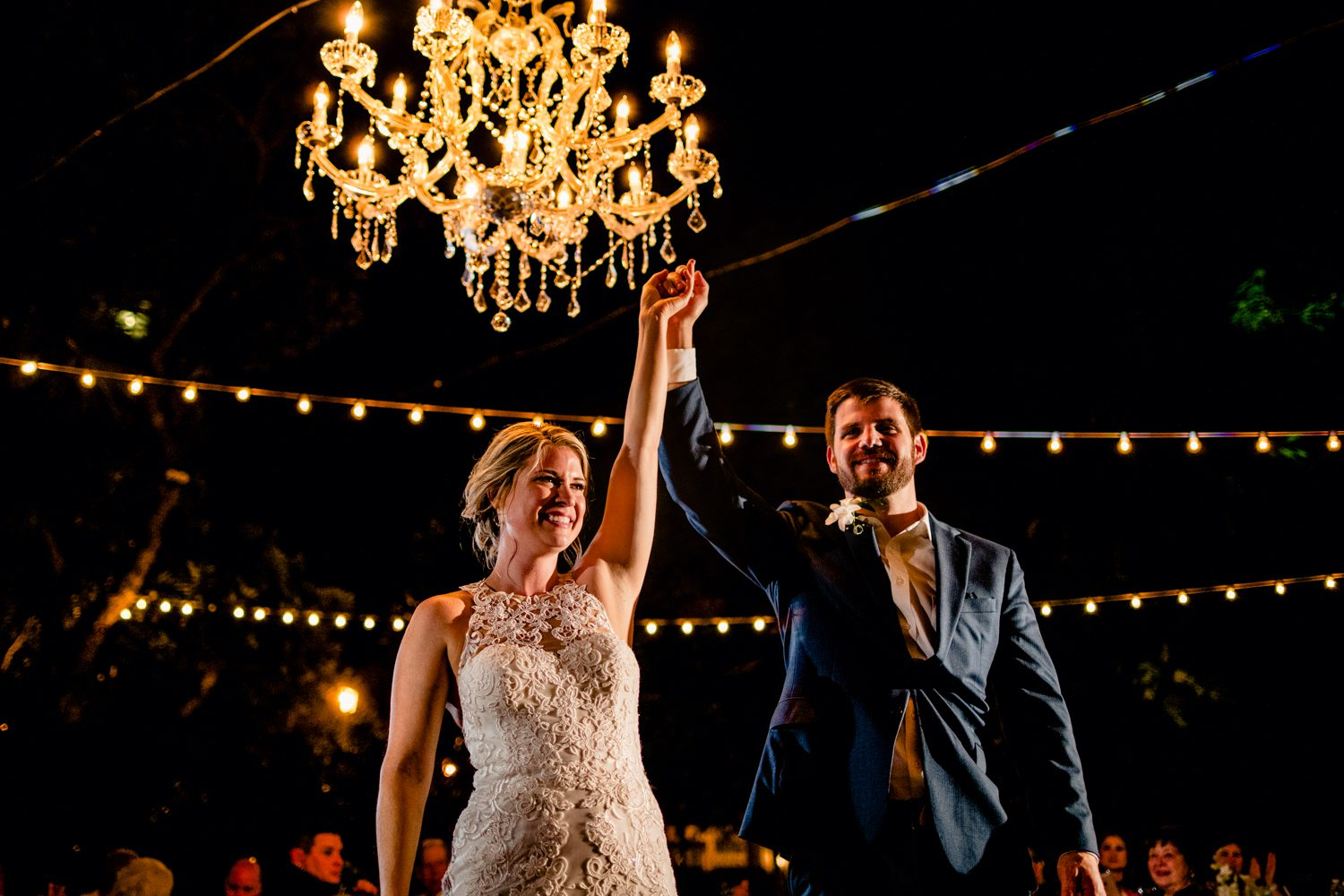 Bride and groom at reception holding their hands above their head