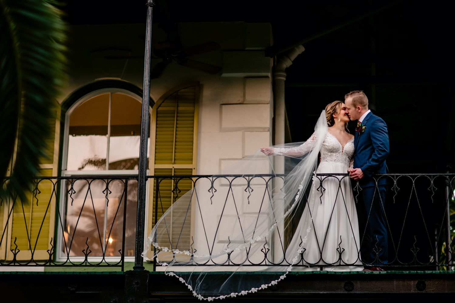 Bride and groom taking a portrait leaning against railing at hemingway house