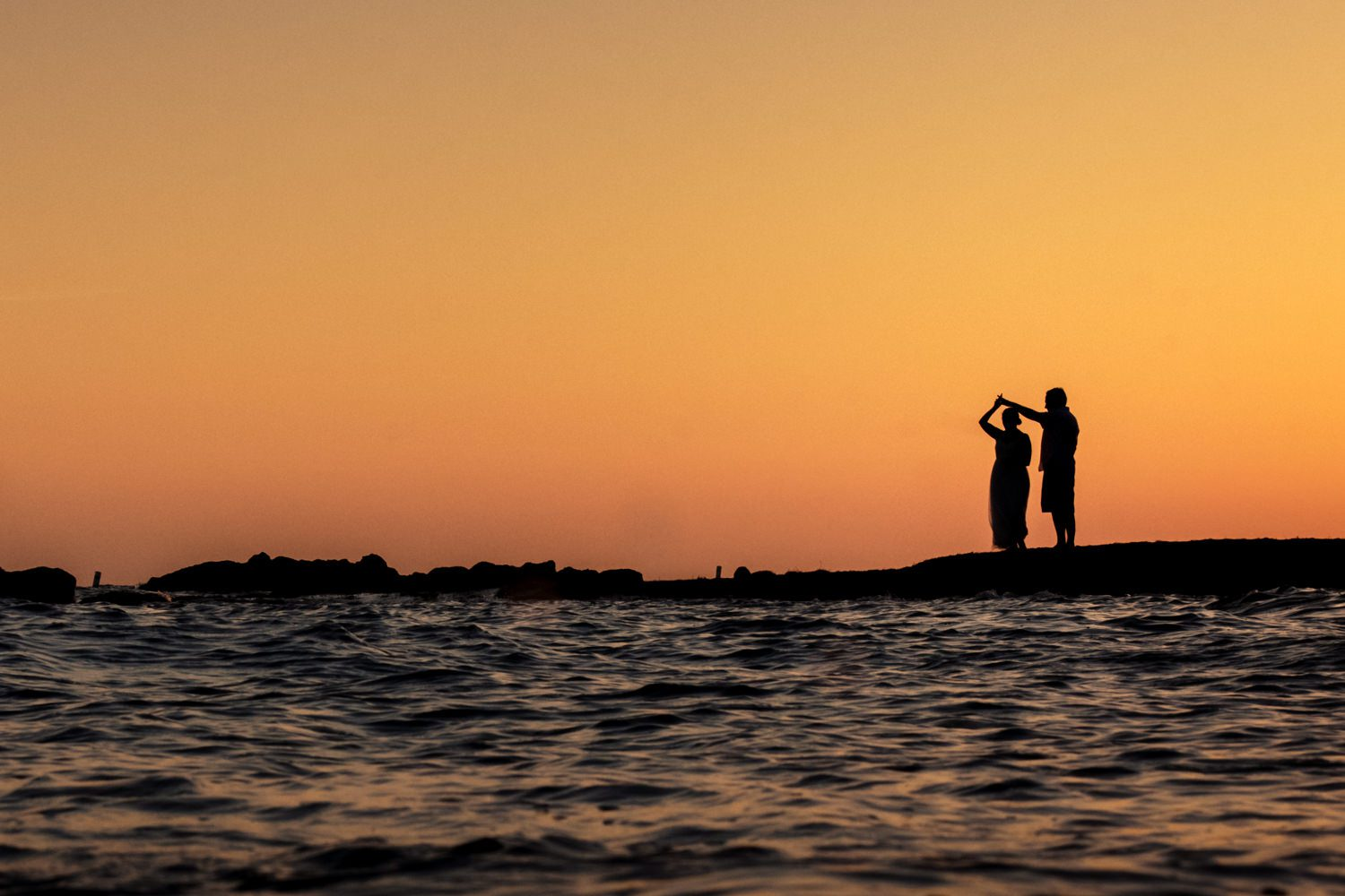 Silhouette of bride and groom kissing on the beach with the sunset in the background of key west.
