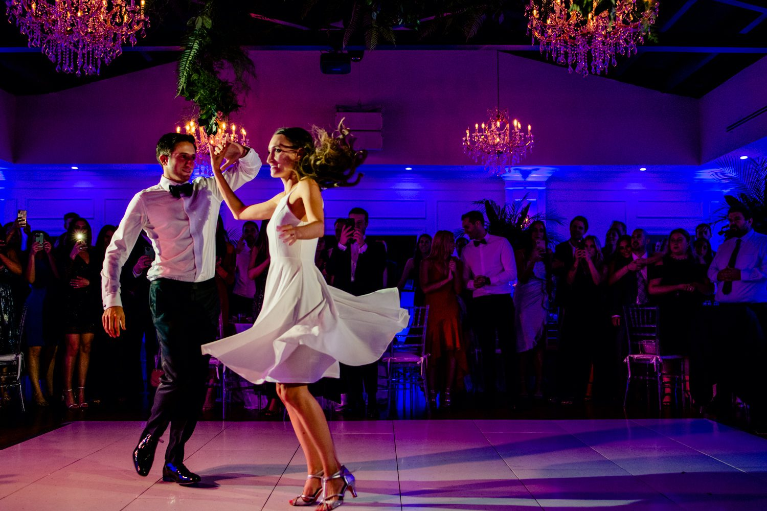 Groom twirling his bride while dancing at their miami wedding