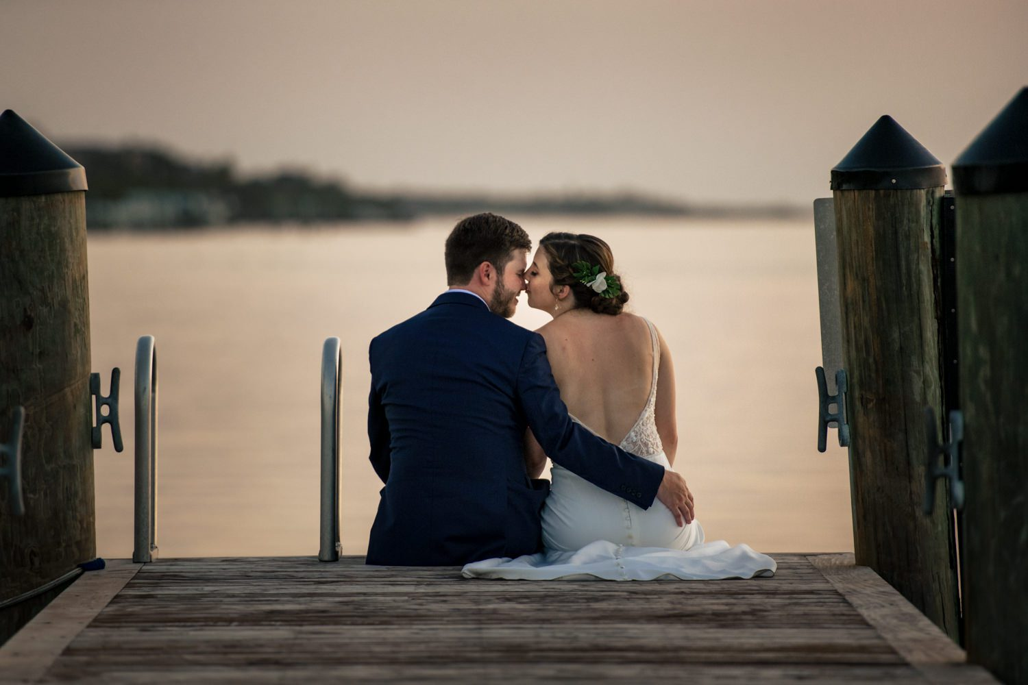 Newlywed couple sitting on a pier in playa largo