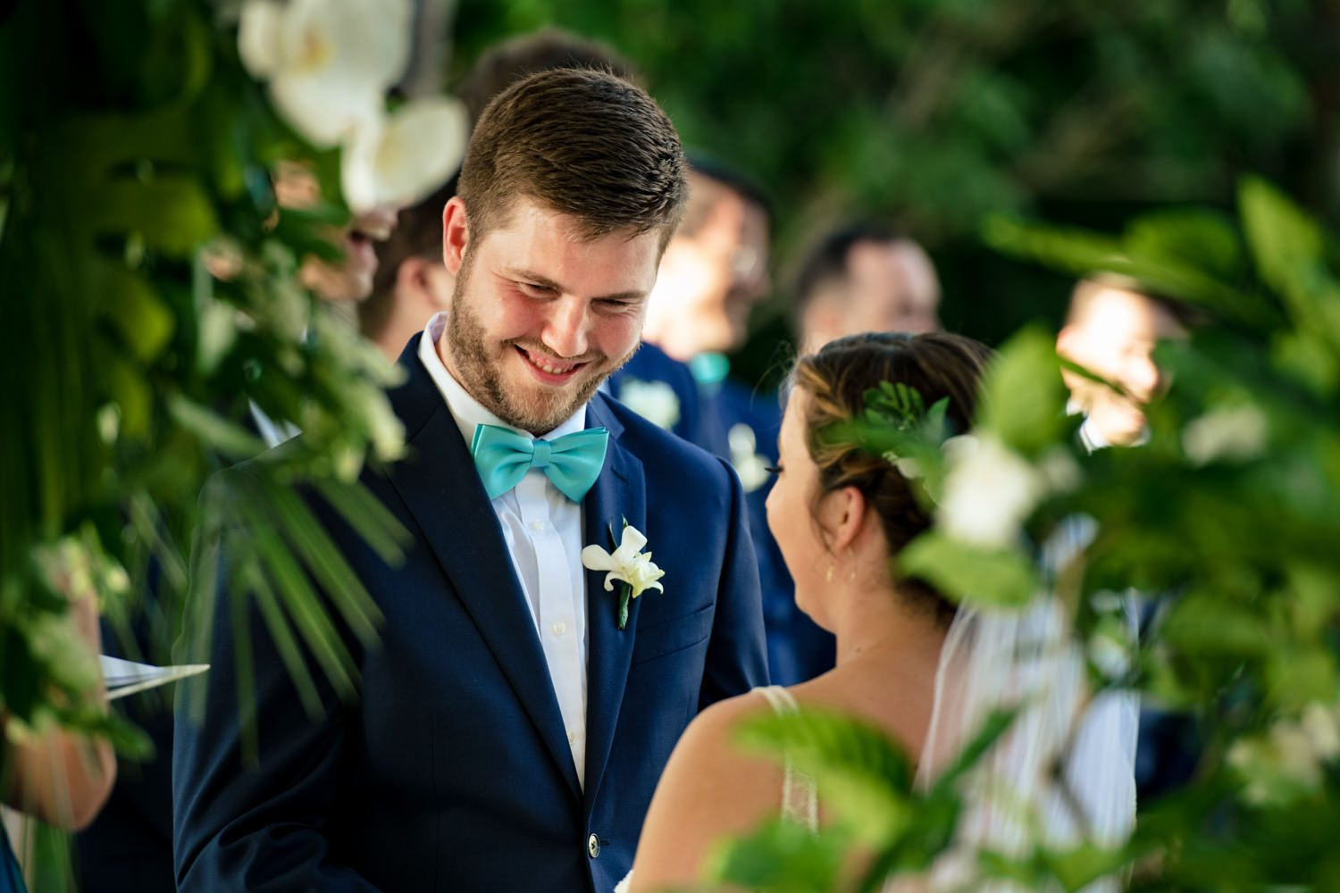 Groom smiling at his bride while exchanging vows