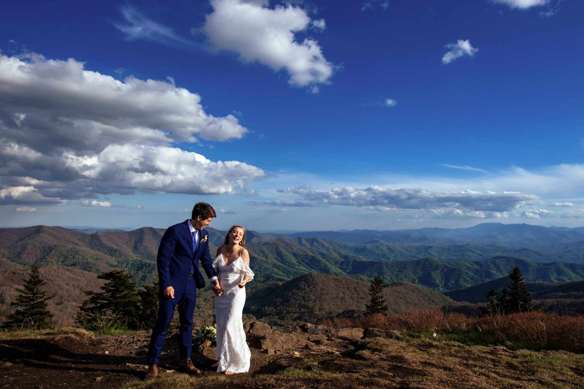 wedding couple laughing after ceremony on mountain top