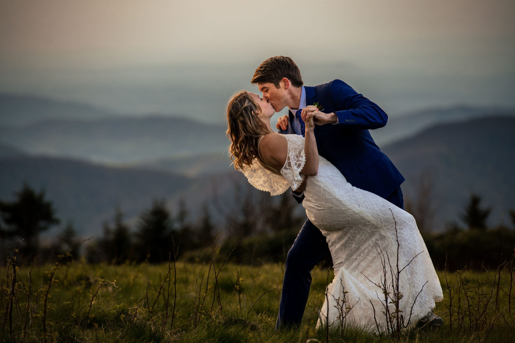 groom dipping bride and kissing on mountain top