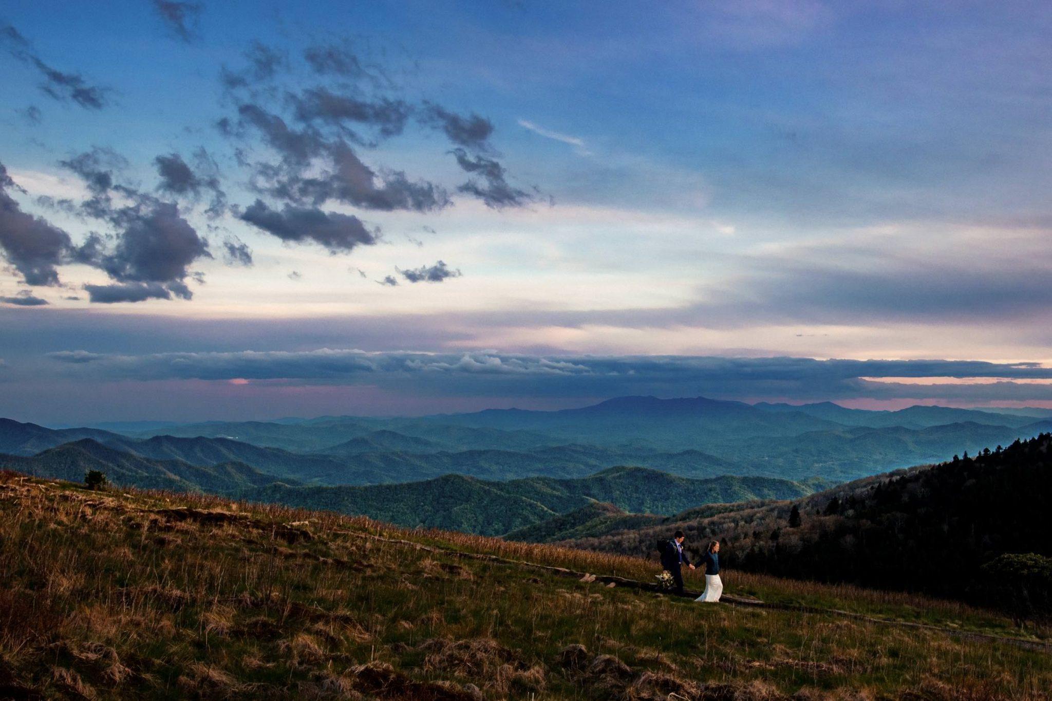 wedding couple walking across mountain top