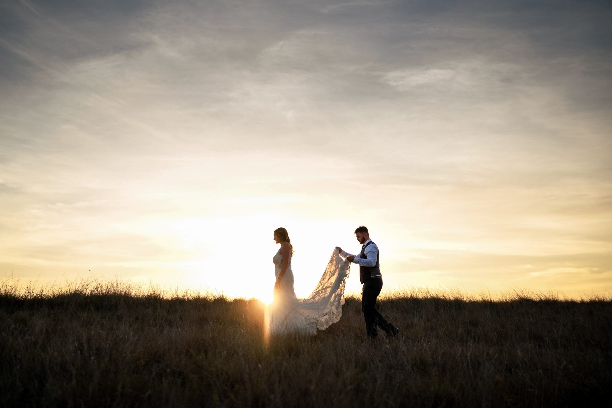groom carrying brides dress across a meadow
