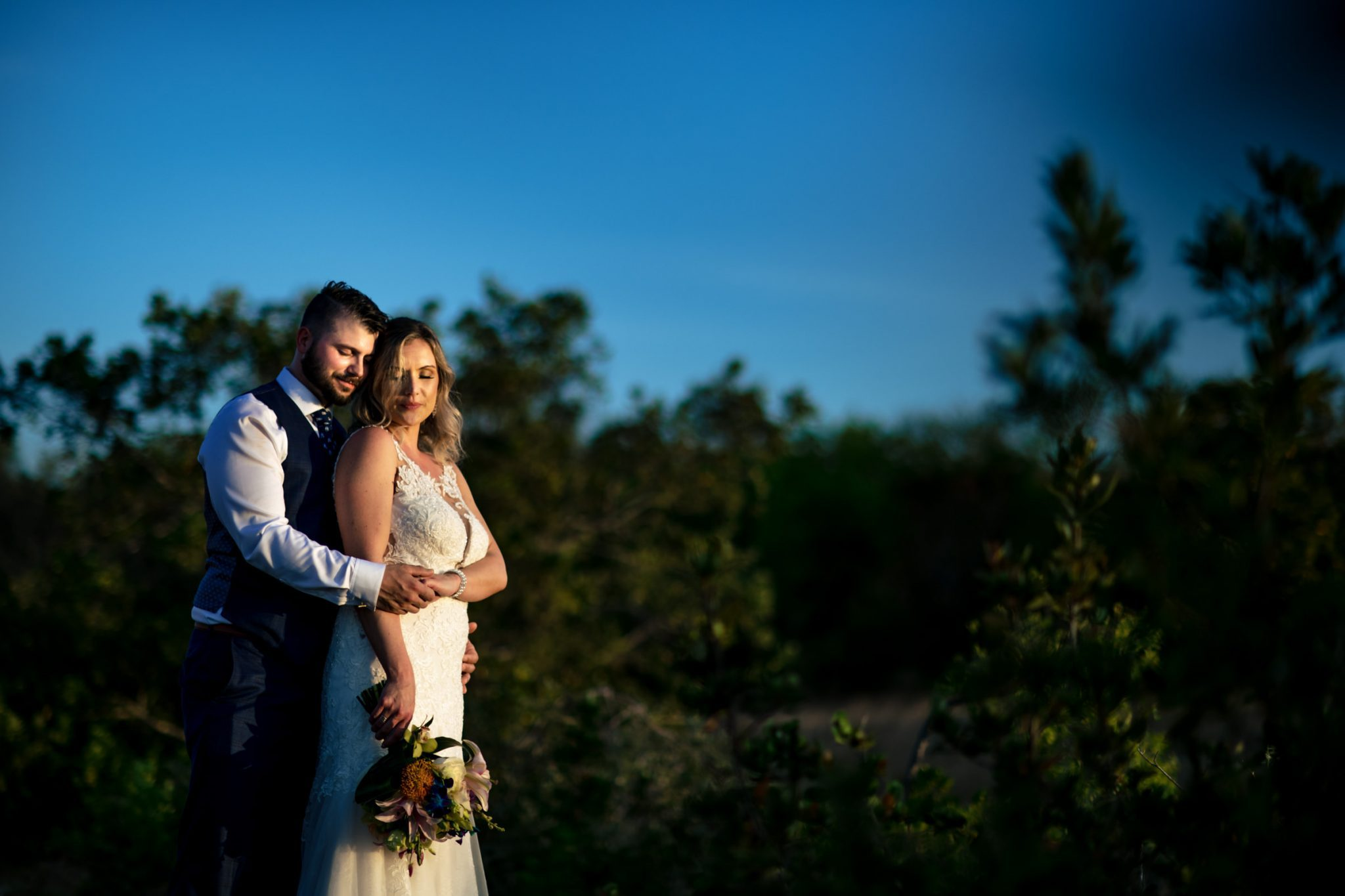 bride and groom on mountain summit at sunset