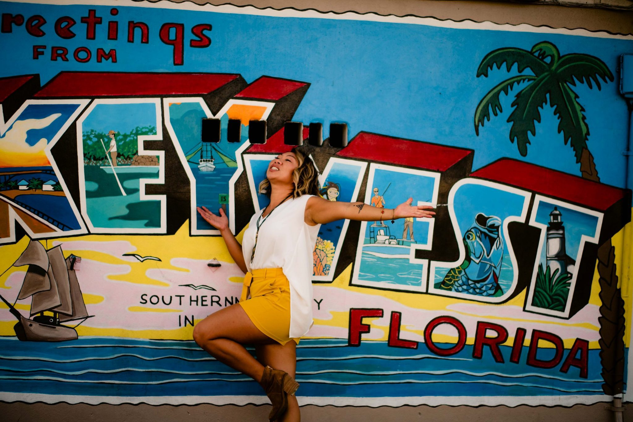 woman jumping in front of a sign for a branding photoshoot in the florida keys