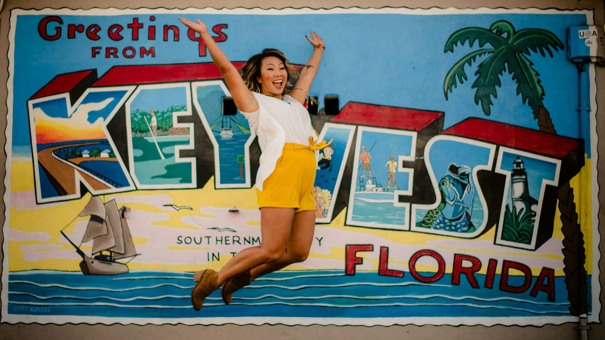 woman jumping in front of a sign for a branding photoshoot