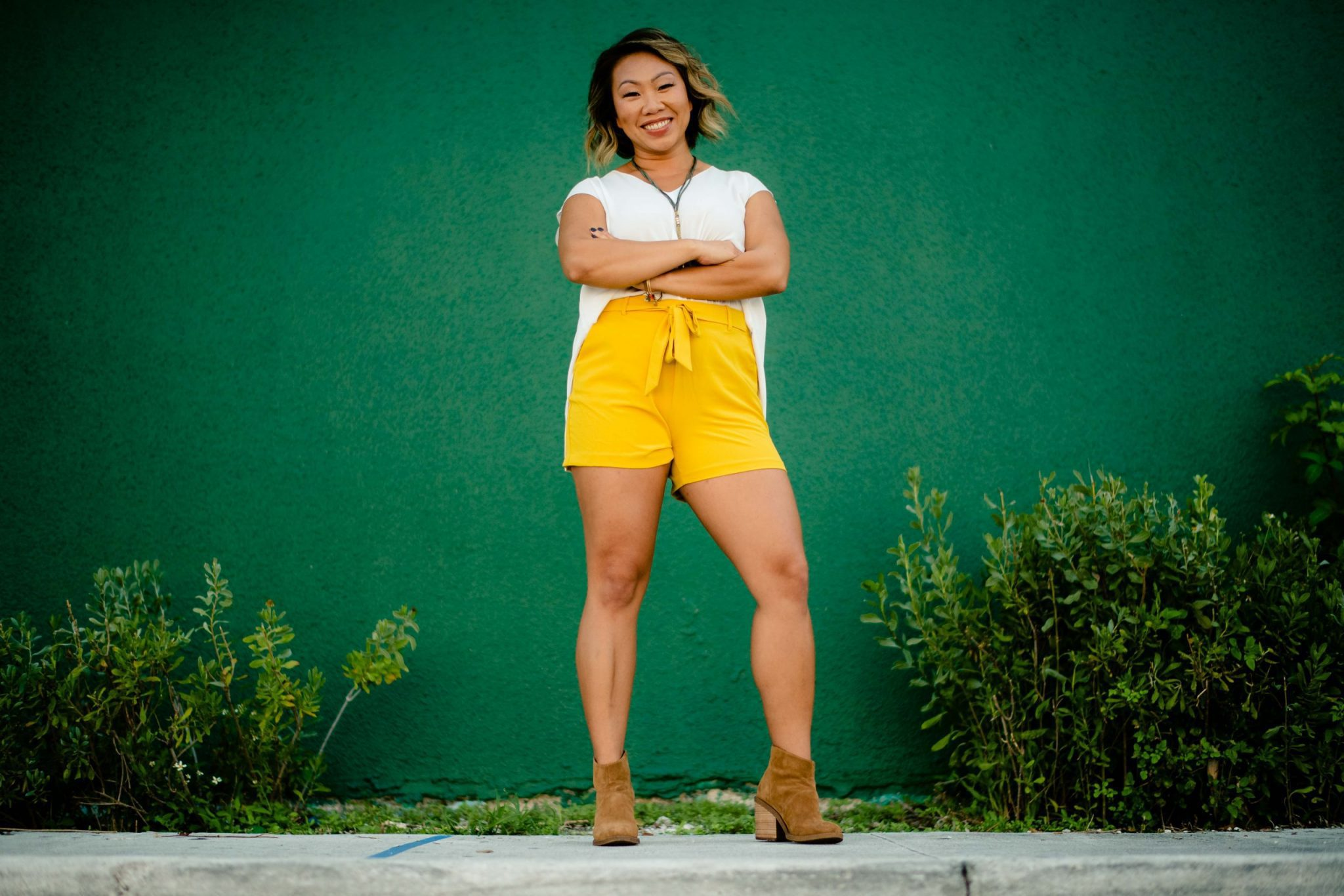 woman in yellow shorts crossing her arms looking camera center for personal branding photography