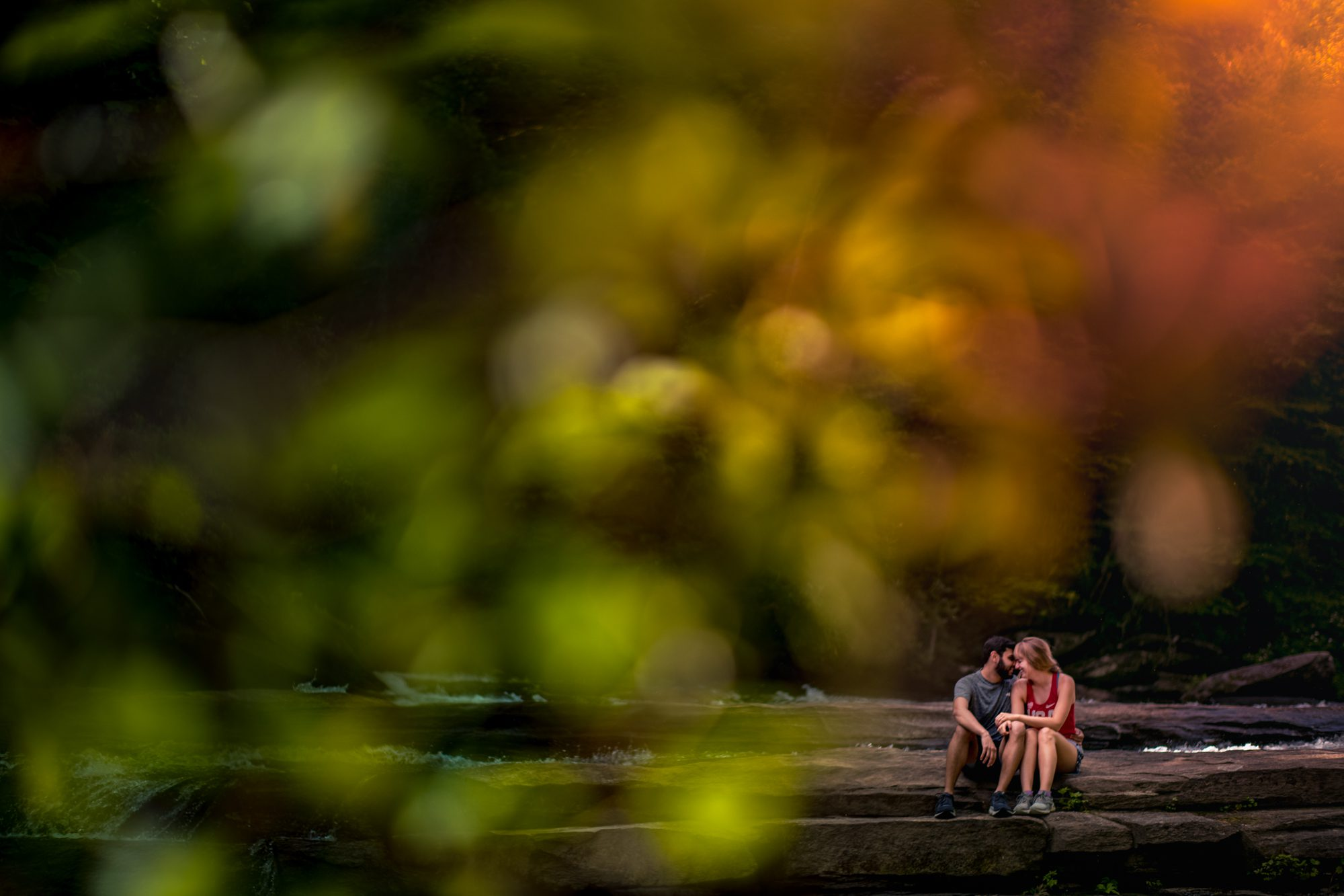 couple sitting on rocks in middle of river