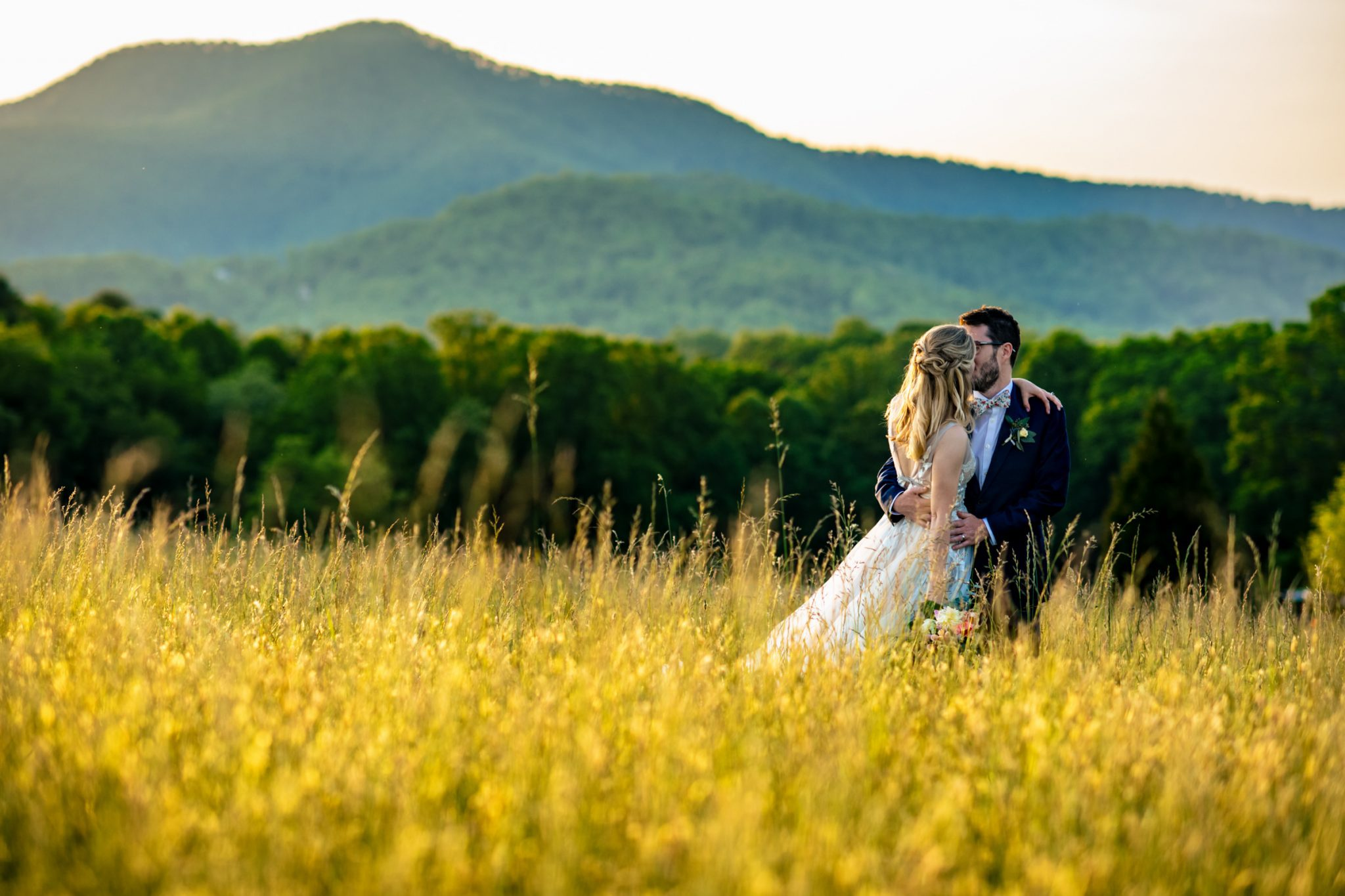 bride and groom kissing in a field with a mountain in the background