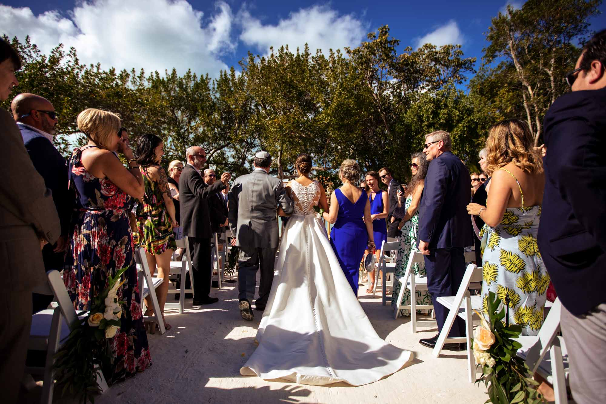 Shot from the back of bride walking down the aisle with her father at bakers cay