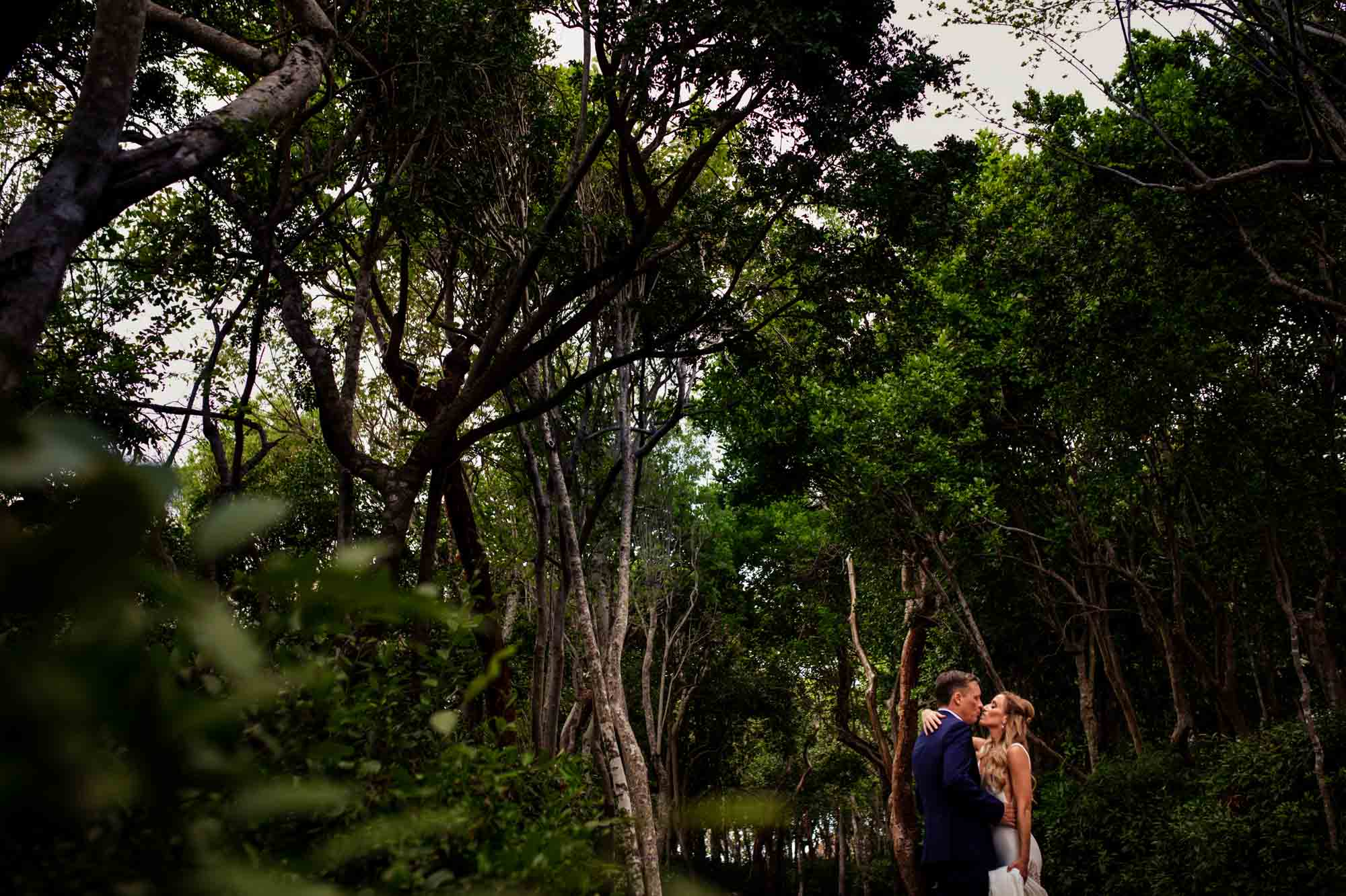 Couple kissing with trees in the background at bakers cay