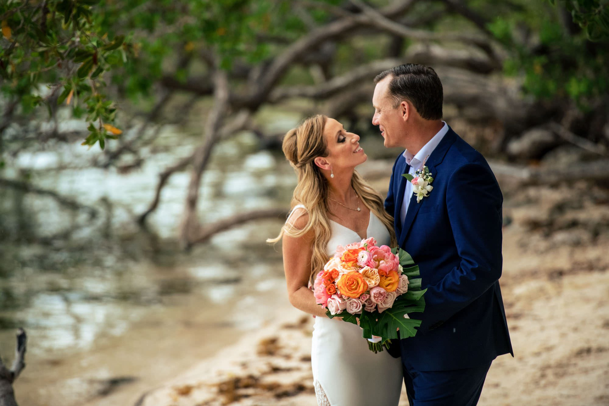 Bride and groom posing on the beach with bouquet at bakers cay