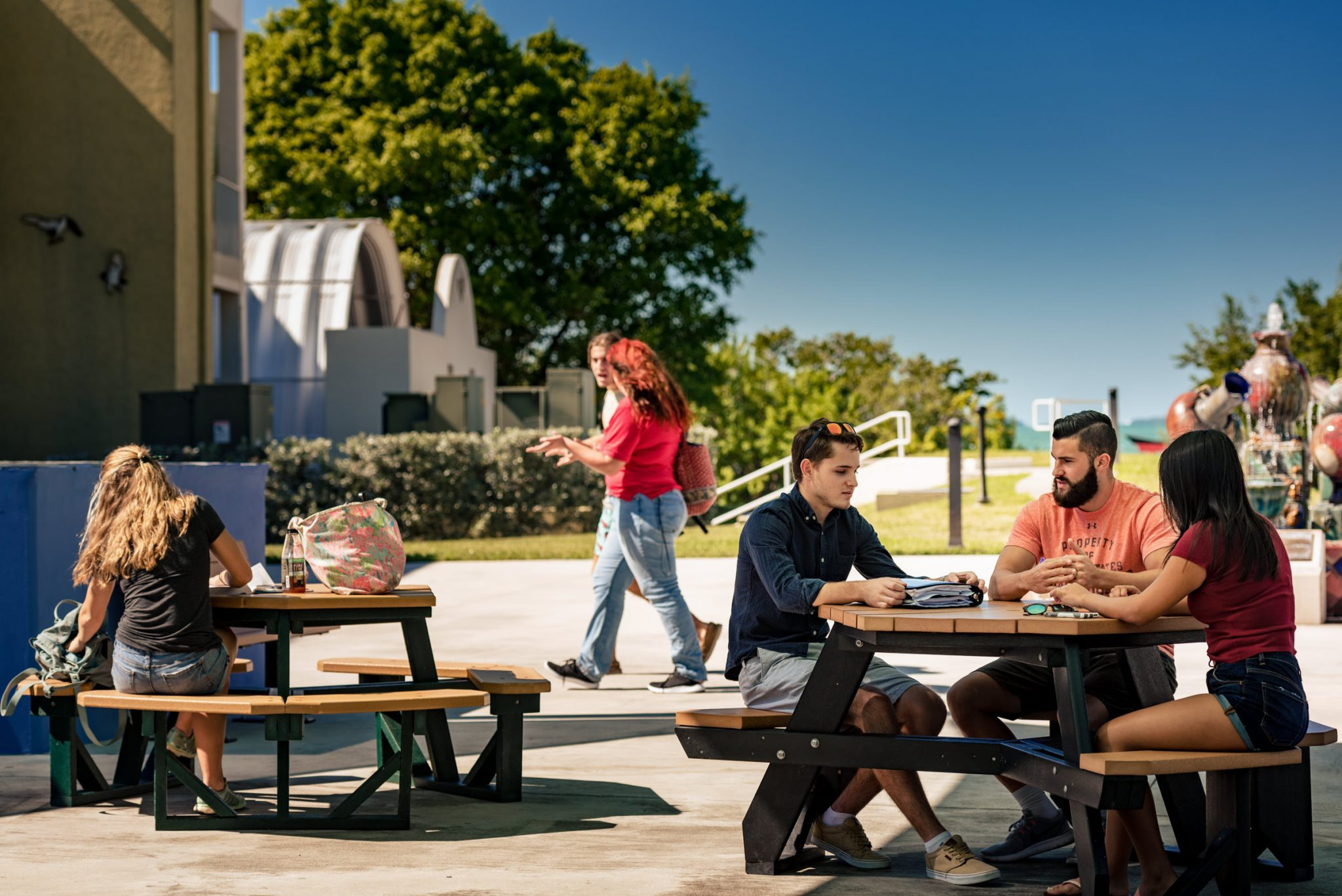 Students siting at outdoor tables on a college campus