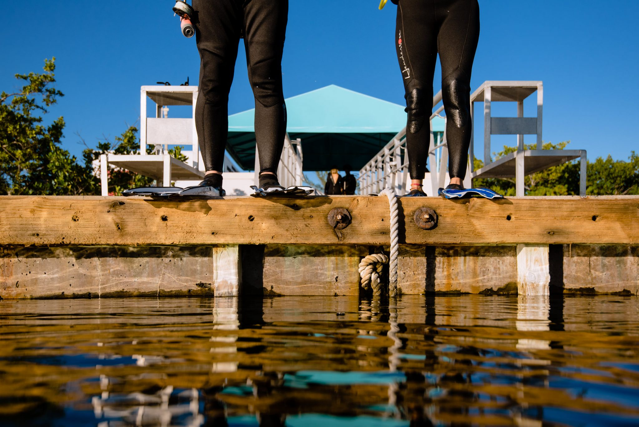 two people about to jump off a pier to go scuba diving