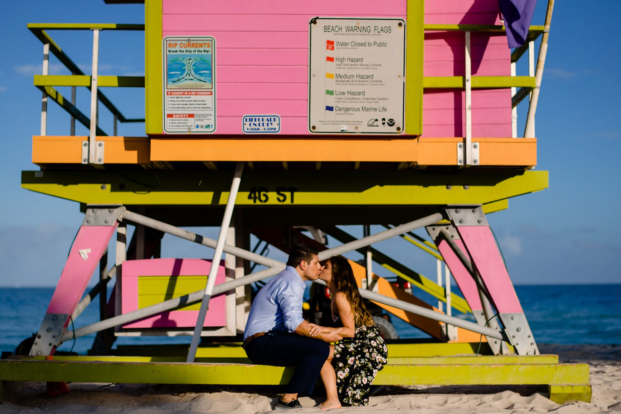 couple sitting on lifeguard stand and kissing