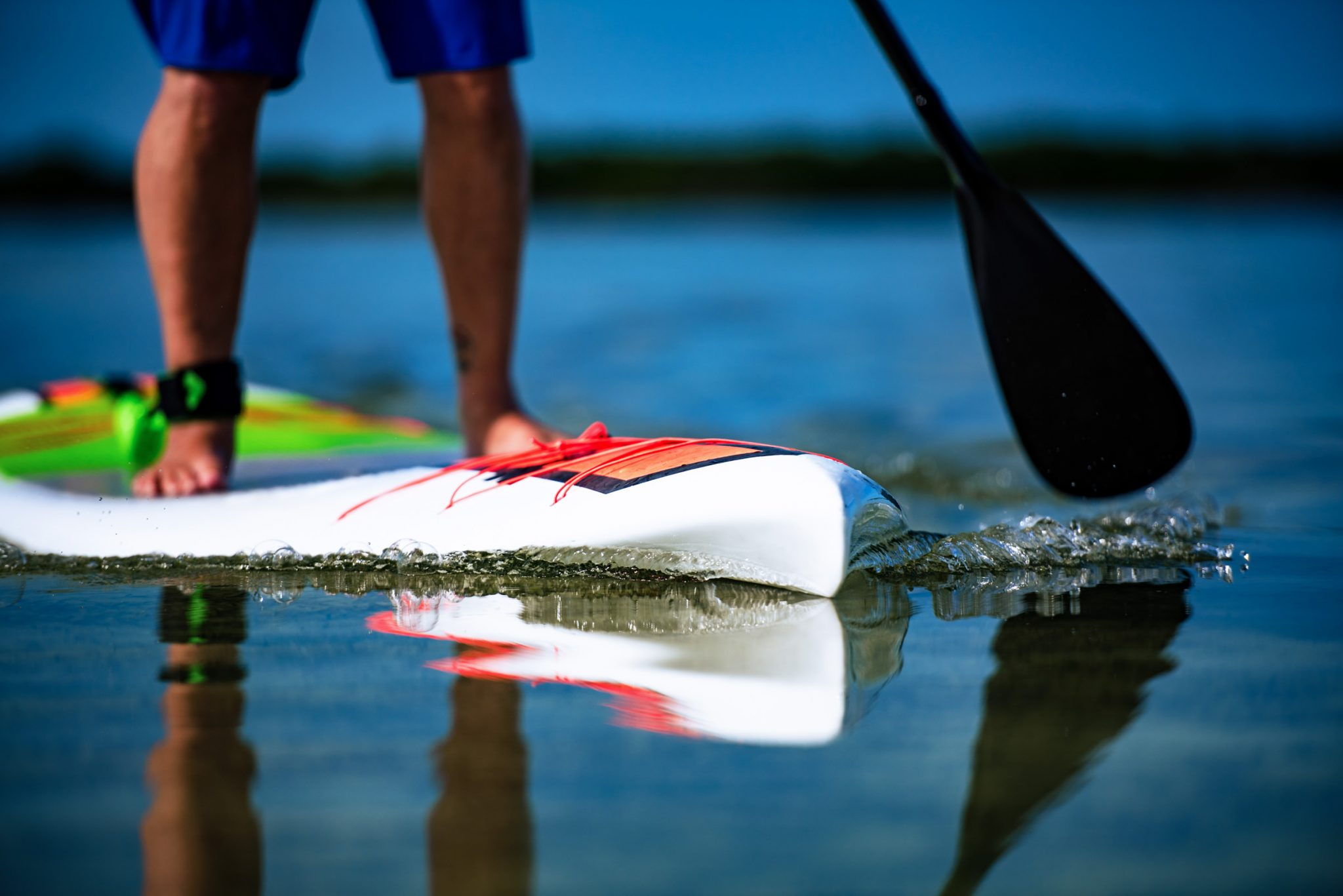 Lower half of man's body standing on a paddle board
