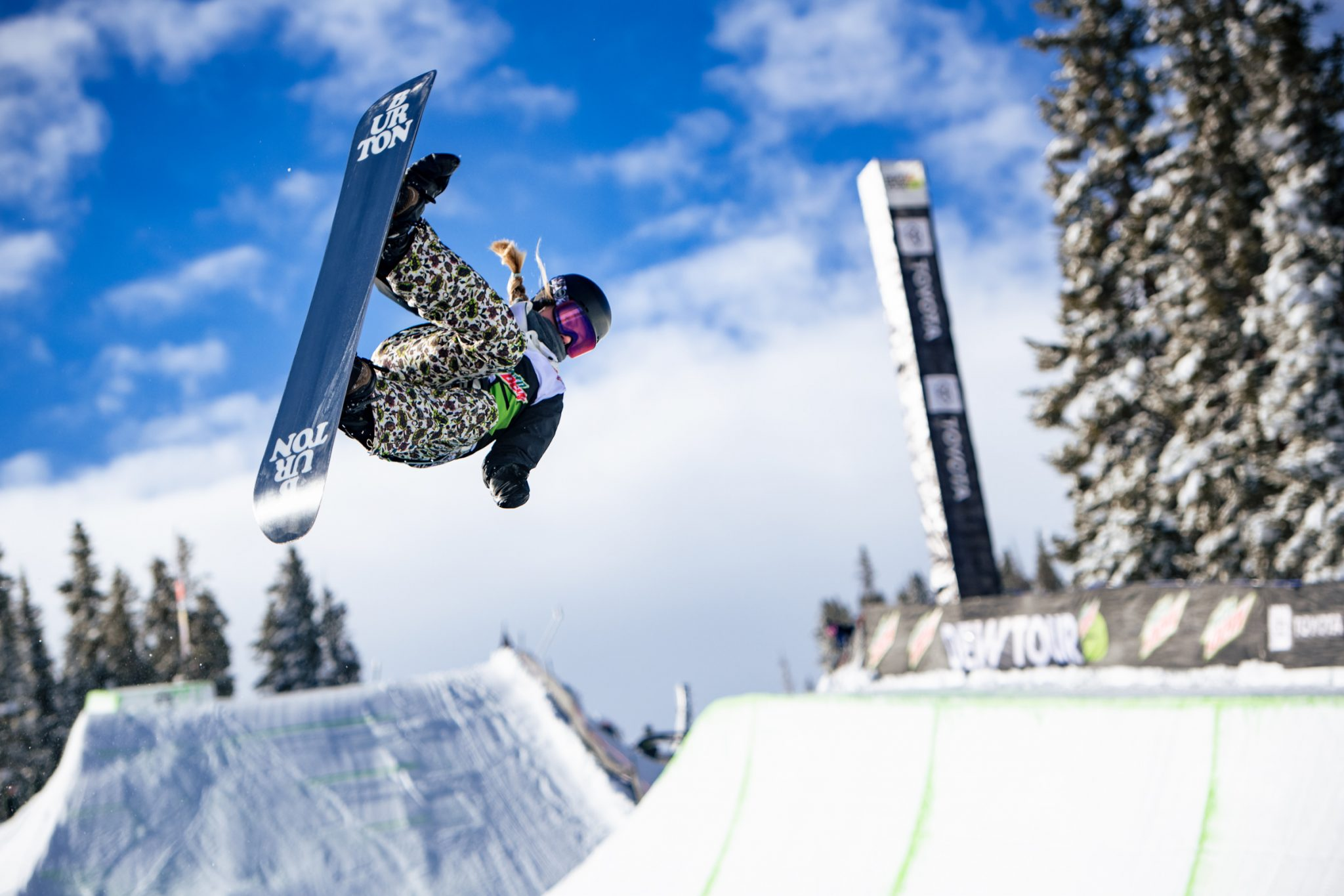 Snowboarder on a half-pipe jumping mid air