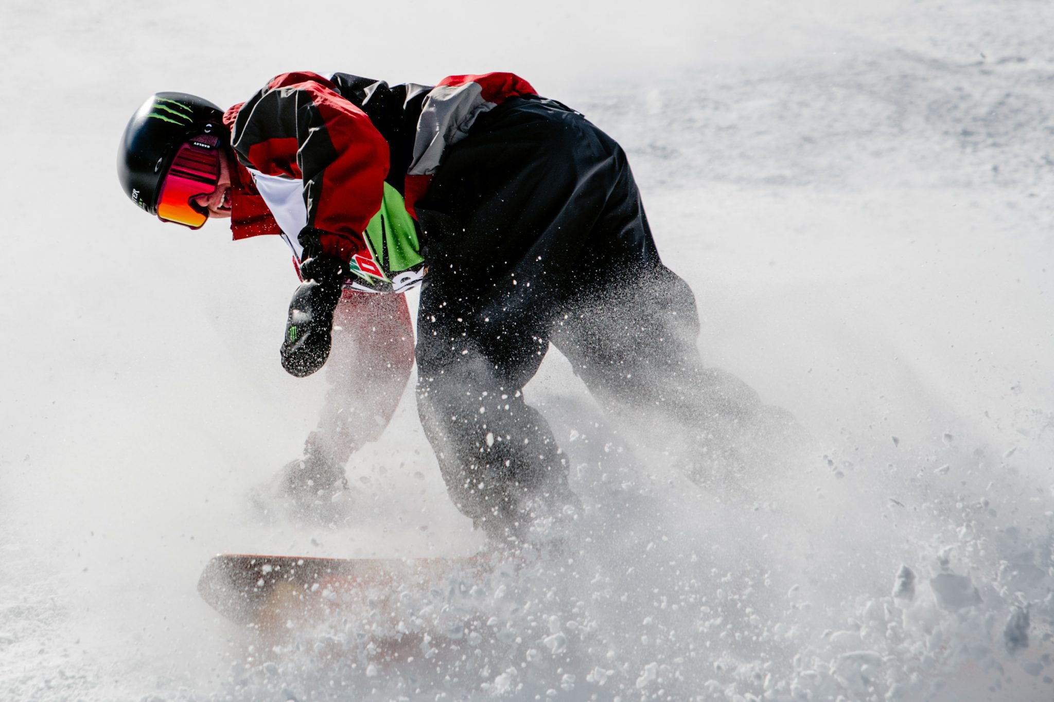 Snowboarder turning and kicking up snow