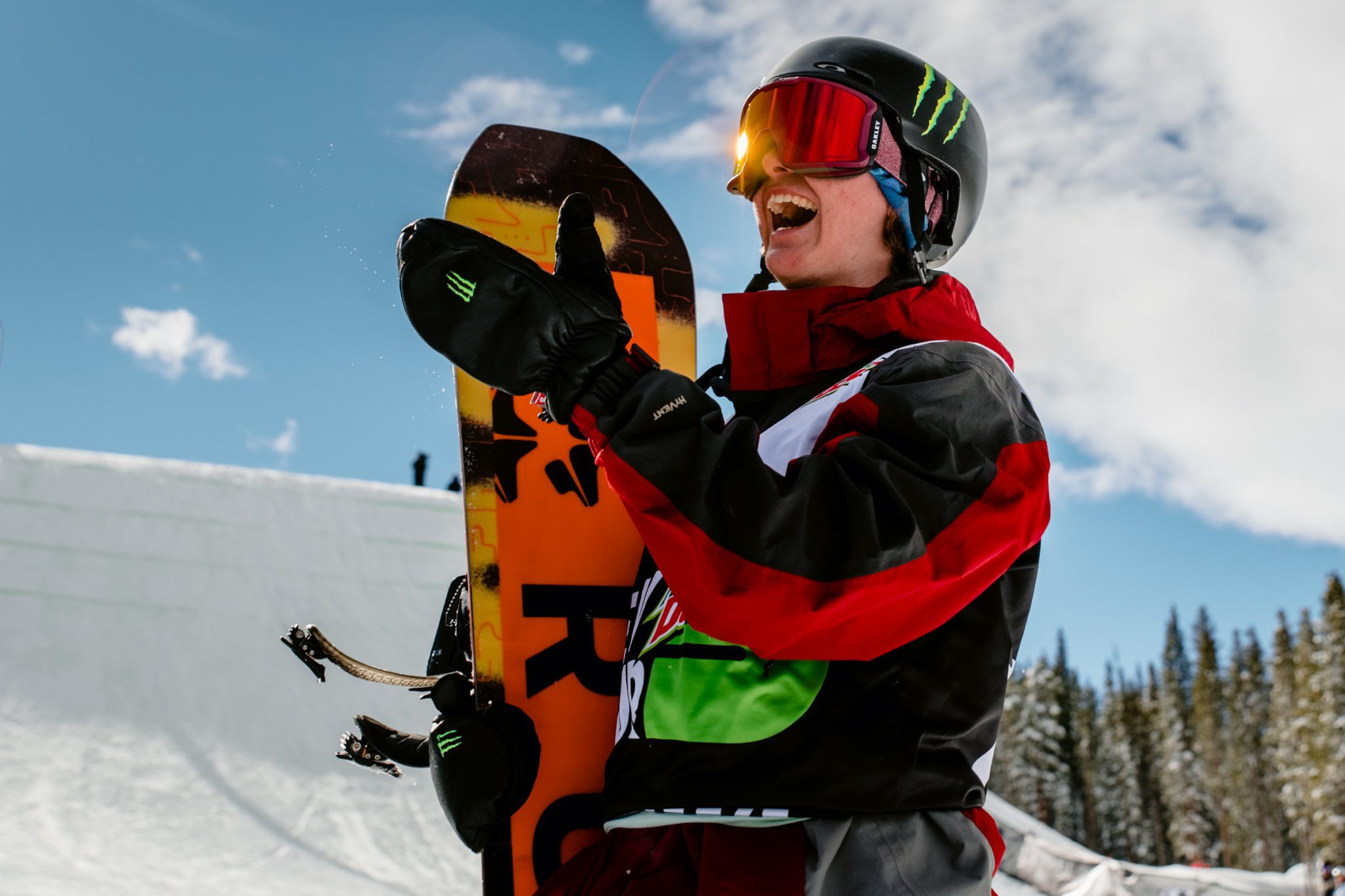 Competitive snowboarder smiling while holding their board